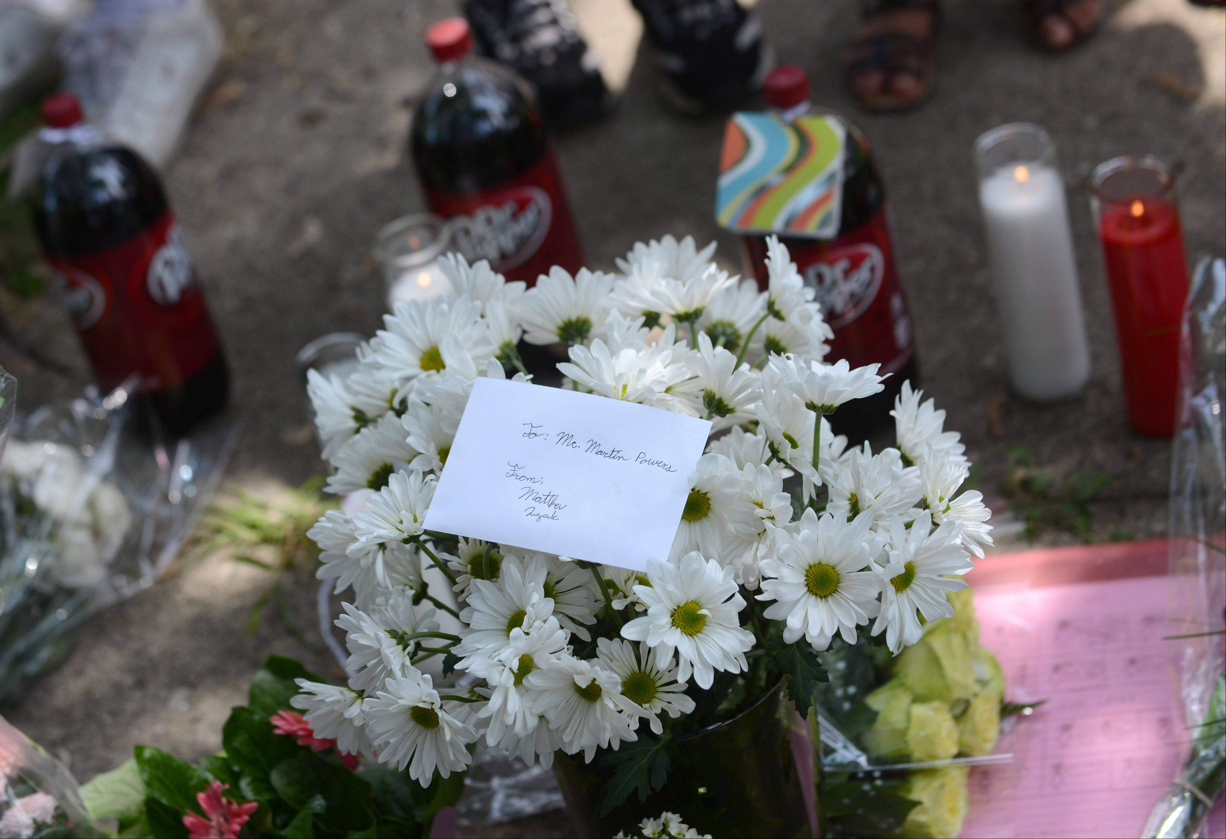 Current and former students left flowers, candles, notes and Dr Pepper, a favorite of Kimball Middle School teacher Martin Powers, at a memorial outside his Elgin home Monday.