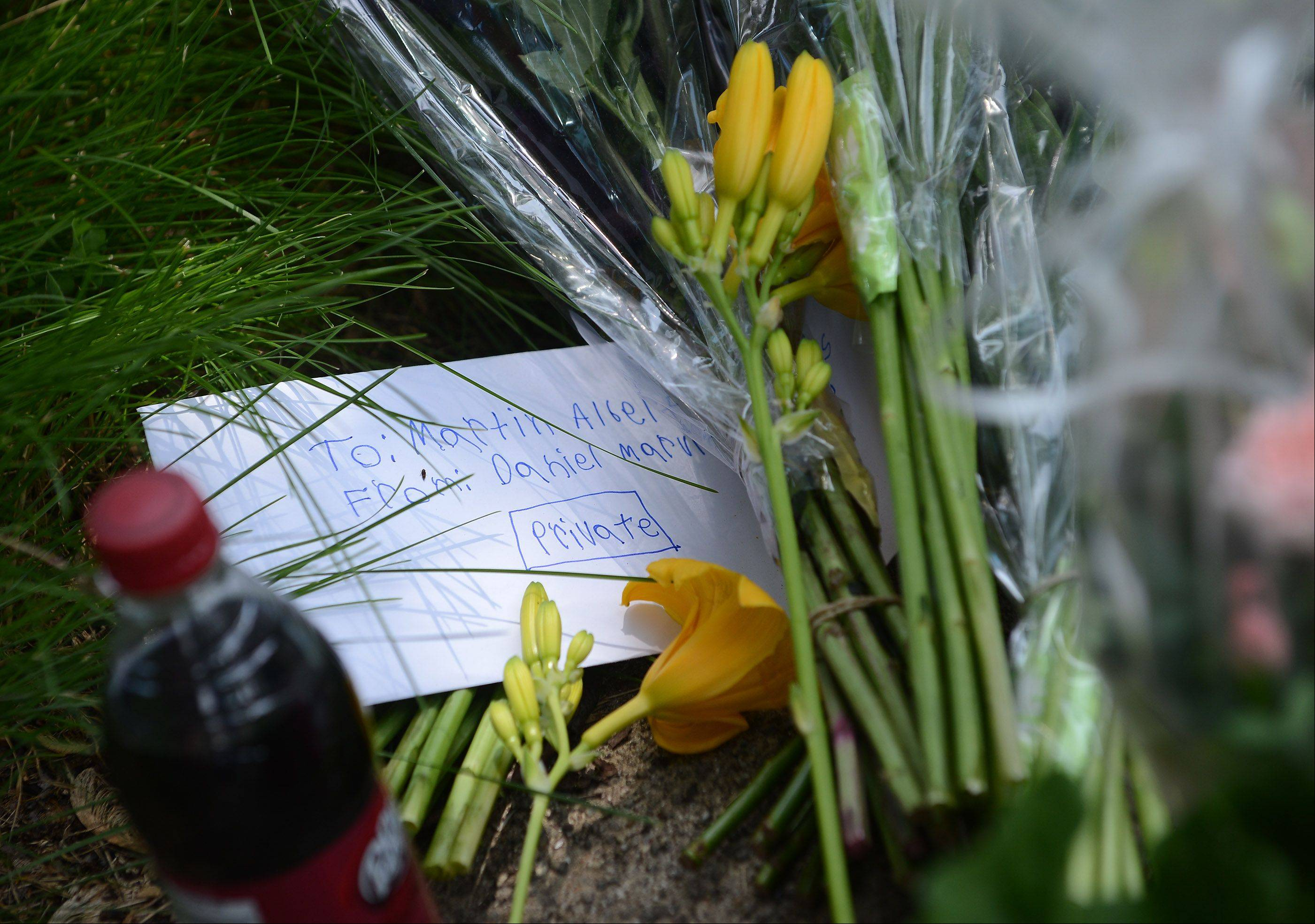 A private note is left at a memorial outside the home of Martin Powers, a teacher at Kimball Middle School.