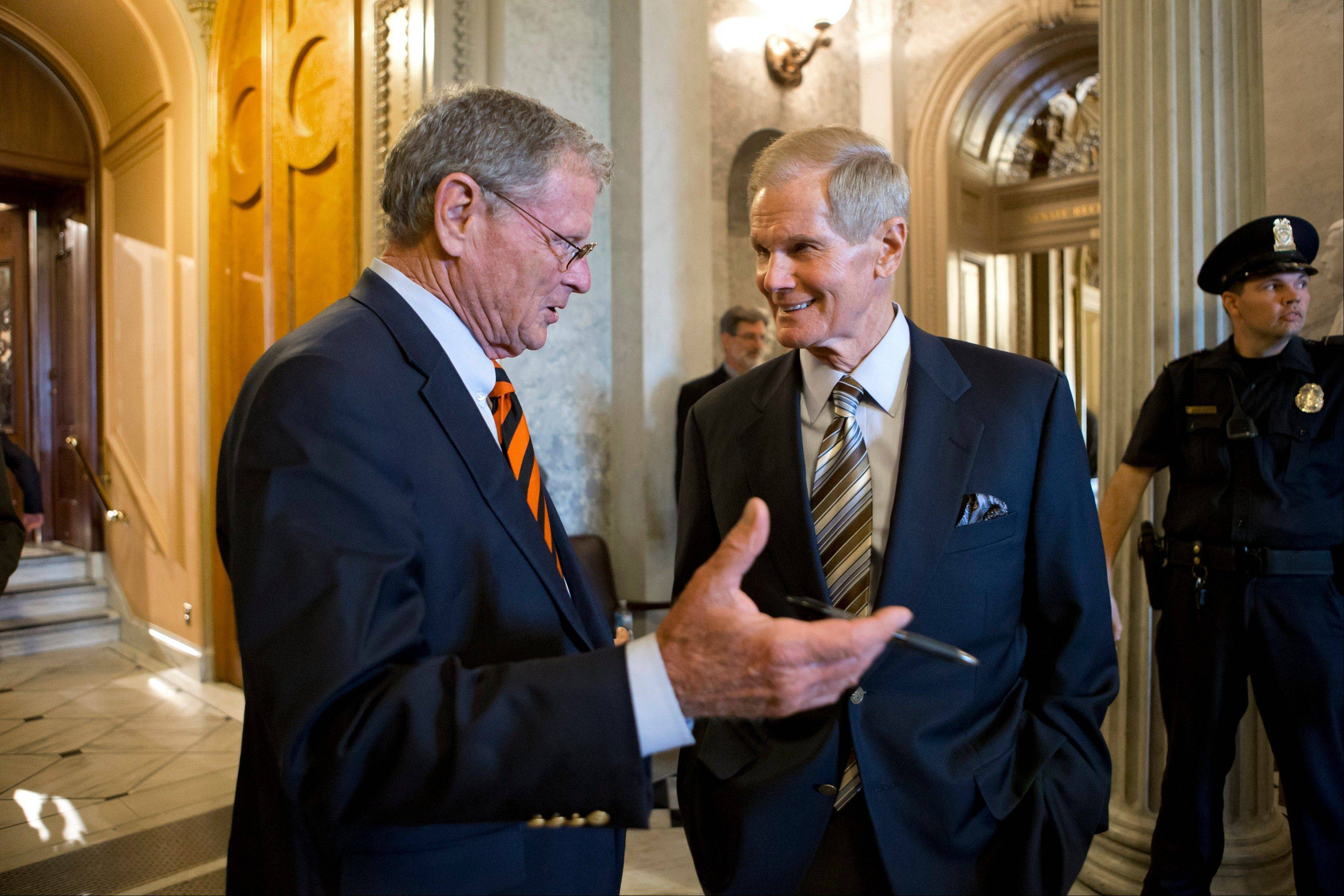 Sen. James Inhofe, an Oklahoma Republican, left, speaks with Sen. Bill Nelson, a Florida Democrat, outside the chamber after the immigration bill got more than 60 needed votes to advance in the Senate on Monday.