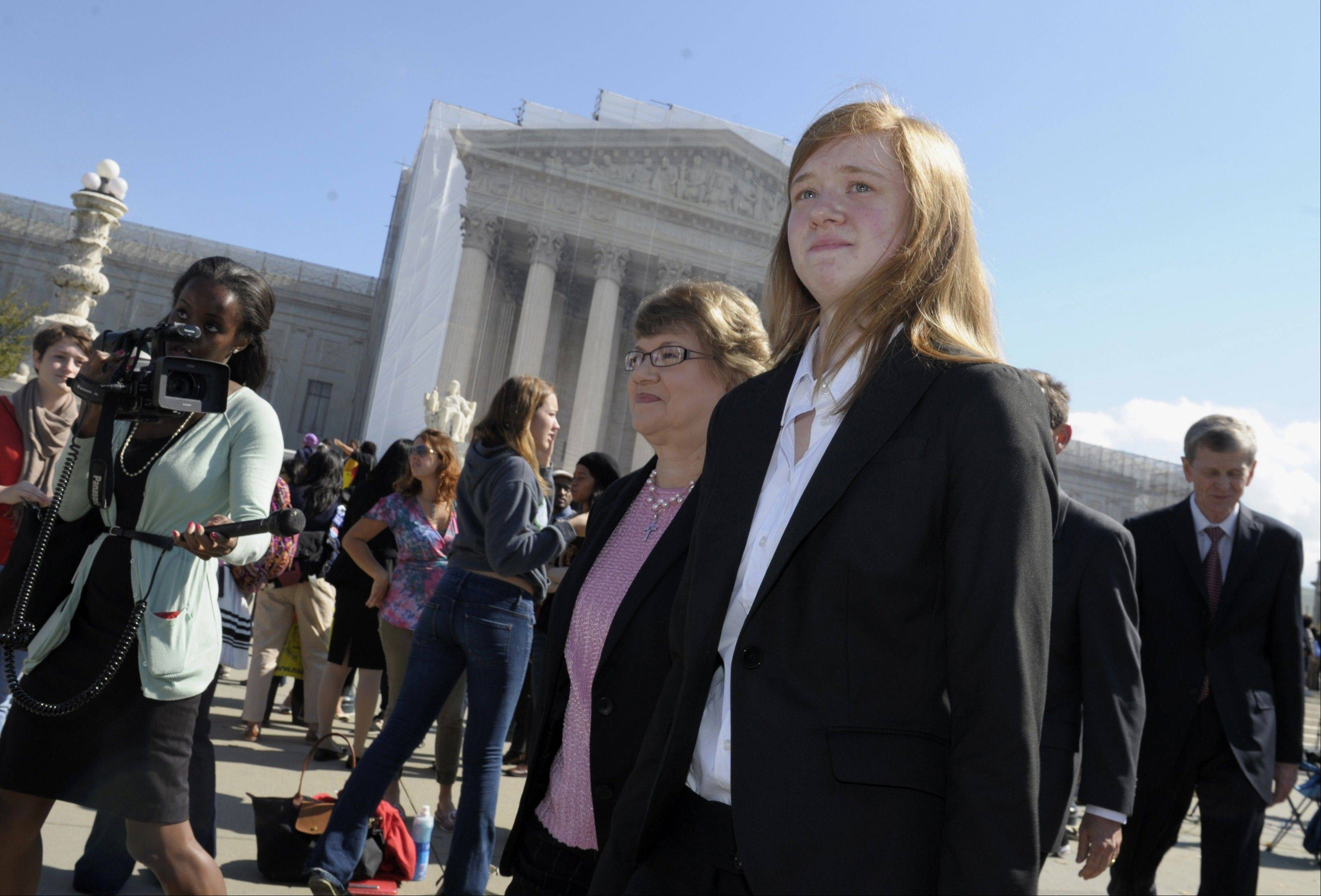 Abigail Fisher, right, who sued the University of Texas, walks outside the Supreme Court in Washington Monday. The Supreme Court has sent a Texas case on race-based college admissions back to a lower court for another look.