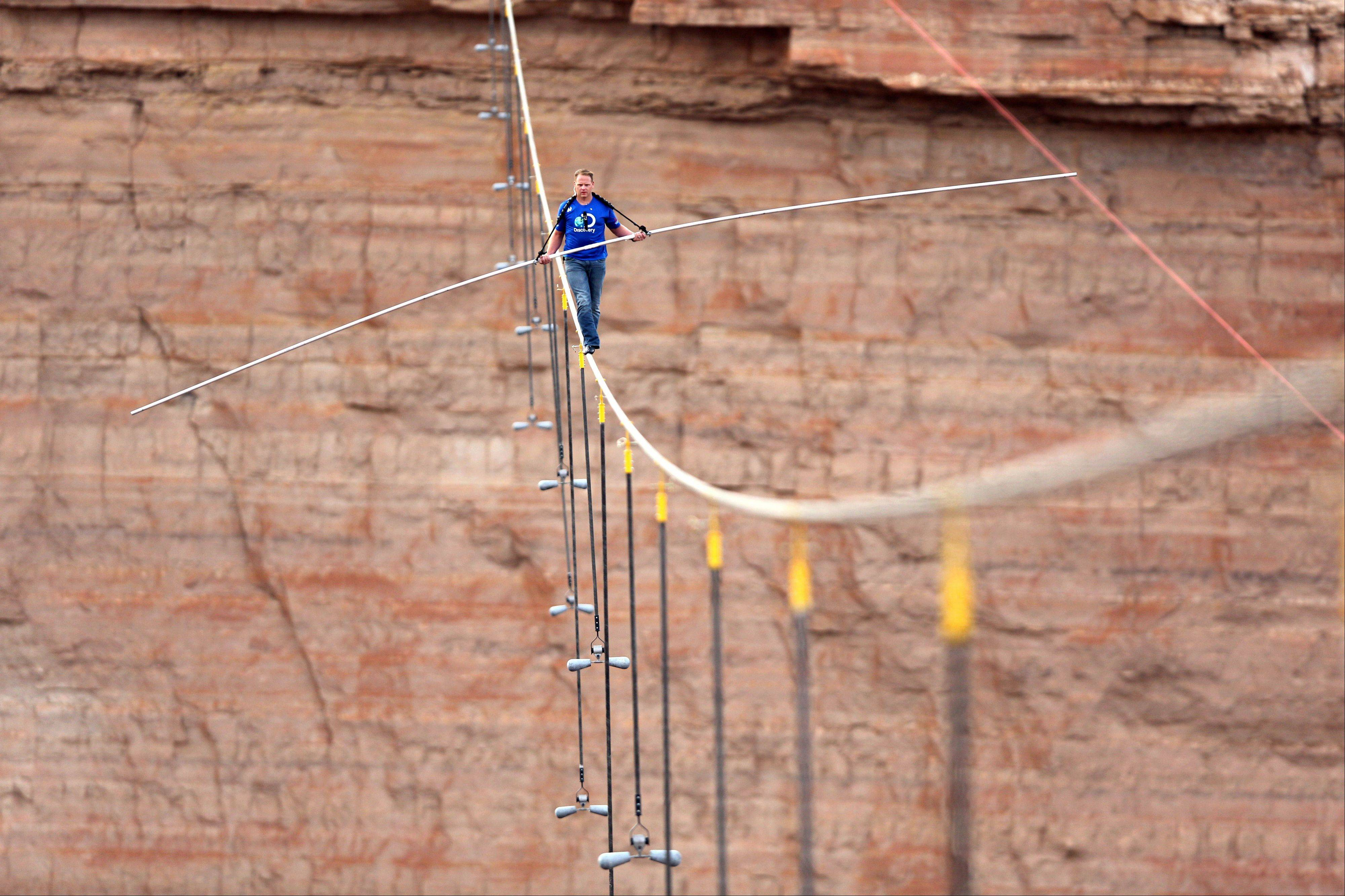 In this photo provided by the Discovery Channel, aerialist Nik Wallenda walks a 2-inch-thick steel cable taking him a quarter mile over the Little Colorado River Gorge, Ariz. on Sunday, June 23, 2013. The daredevil successfully traversed the tightrope strung 1,500 feet above the chasm near the Grand Canyon in just more than 22 minutes, pausing and crouching twice as winds whipped around him and the cable swayed.