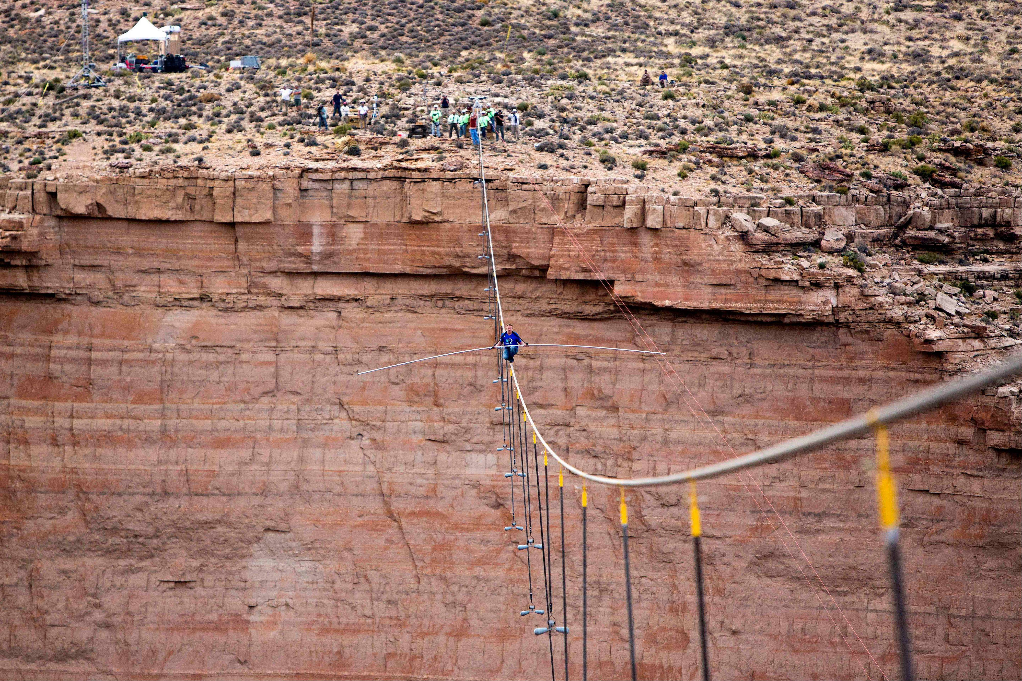 Aerialist Nik Wallenda pauses during his quarter mile walk over the Little Colorado River Gorge in northeastern Arizona on Sunday, June 23, 2013. The daredevil successfully traversed a tightrope strung 1,500 feet above the chasm near the Grand Canyon in just more than 22 minutes, pausing and crouching twice as winds whipped around him and the cable swayed.