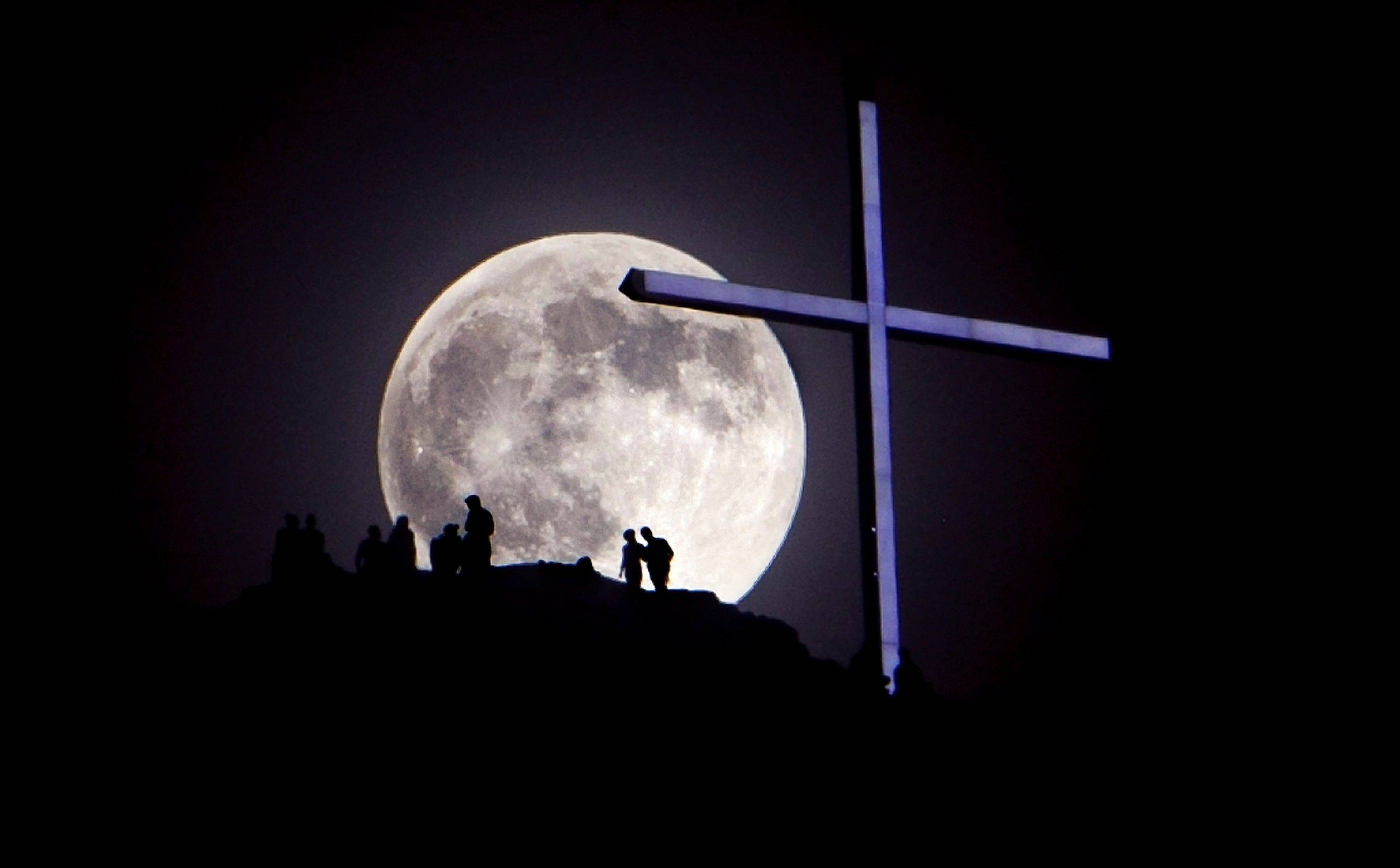 "A ""supermoon"" rises over Table Rock and the lighted cross near Boise, Idaho, Saturday night, June 22, 2013. The larger than normal moon called the ""Supermoon"" happens only once this year as the moon on its elliptical orbit is at its closest point to earth and appears 13.5 percent larger than usual."