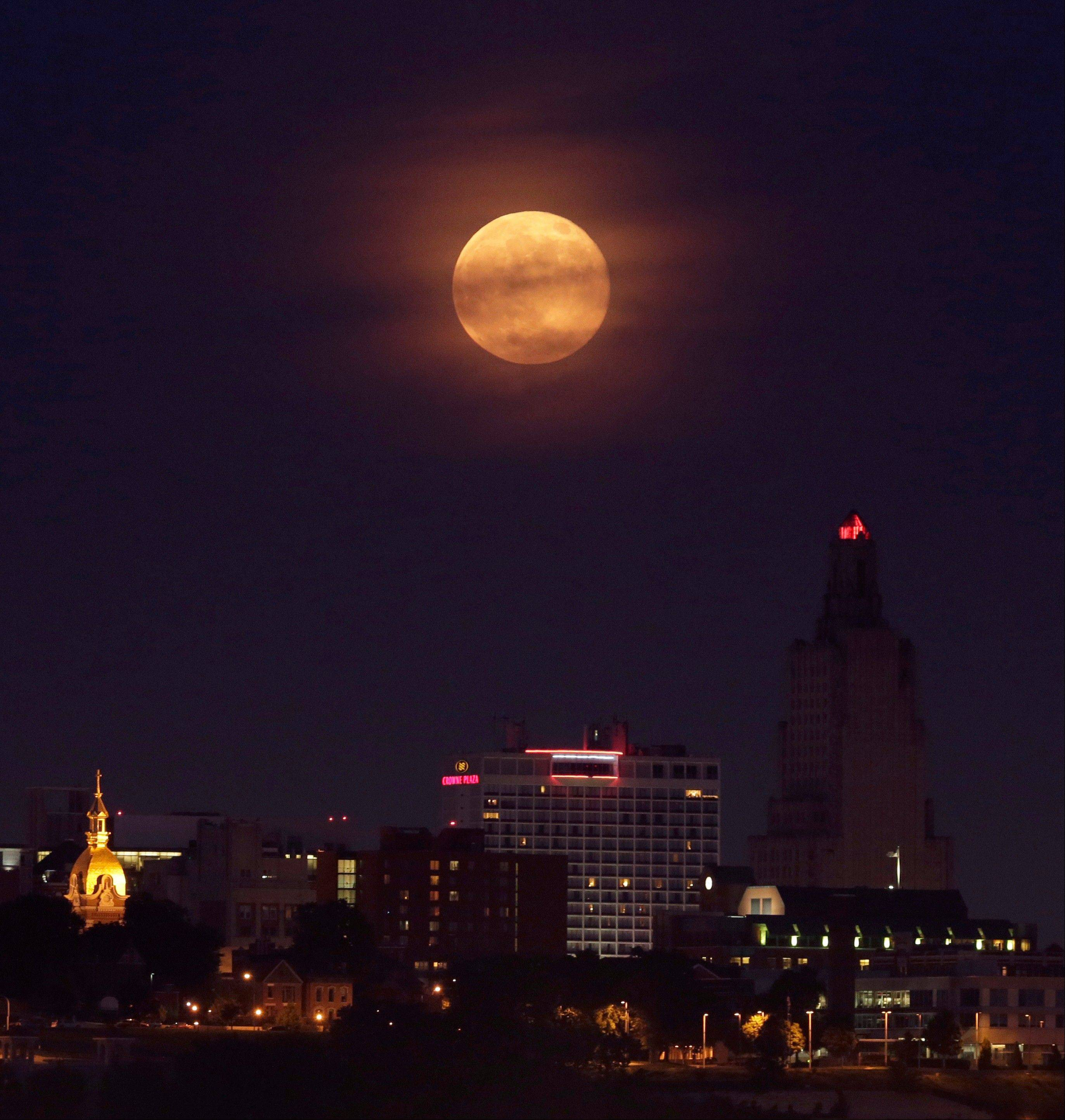A full moon rises through clouds behind downtown buildings Sunday, June 23, 2013, in Kansas City, Mo. The so-called supermoon appeared up to 14 percent larger than normal as our celestial neighbor swung closer to Earth, reaching its closest distance early Sunday morning.