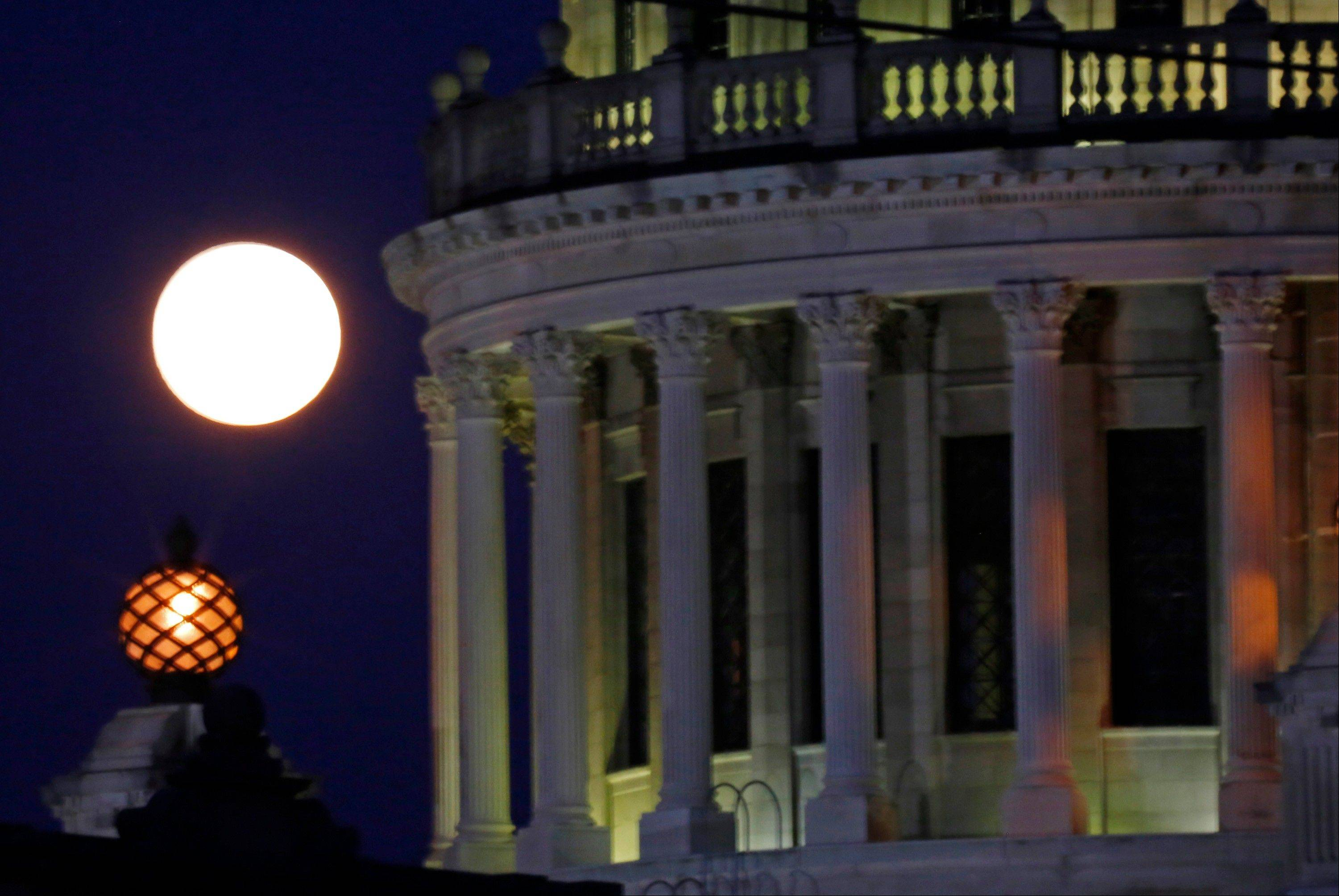 A full moon sets by the exterior of the state Capitol in Jackson, Miss., Sunday morning, June 23, 2013. The moon, which will reach its full stage Sunday, is expected to be significantly closer to earth during a phenomenon known as supermoon. (AP Photo/Rogelio V. Solis)