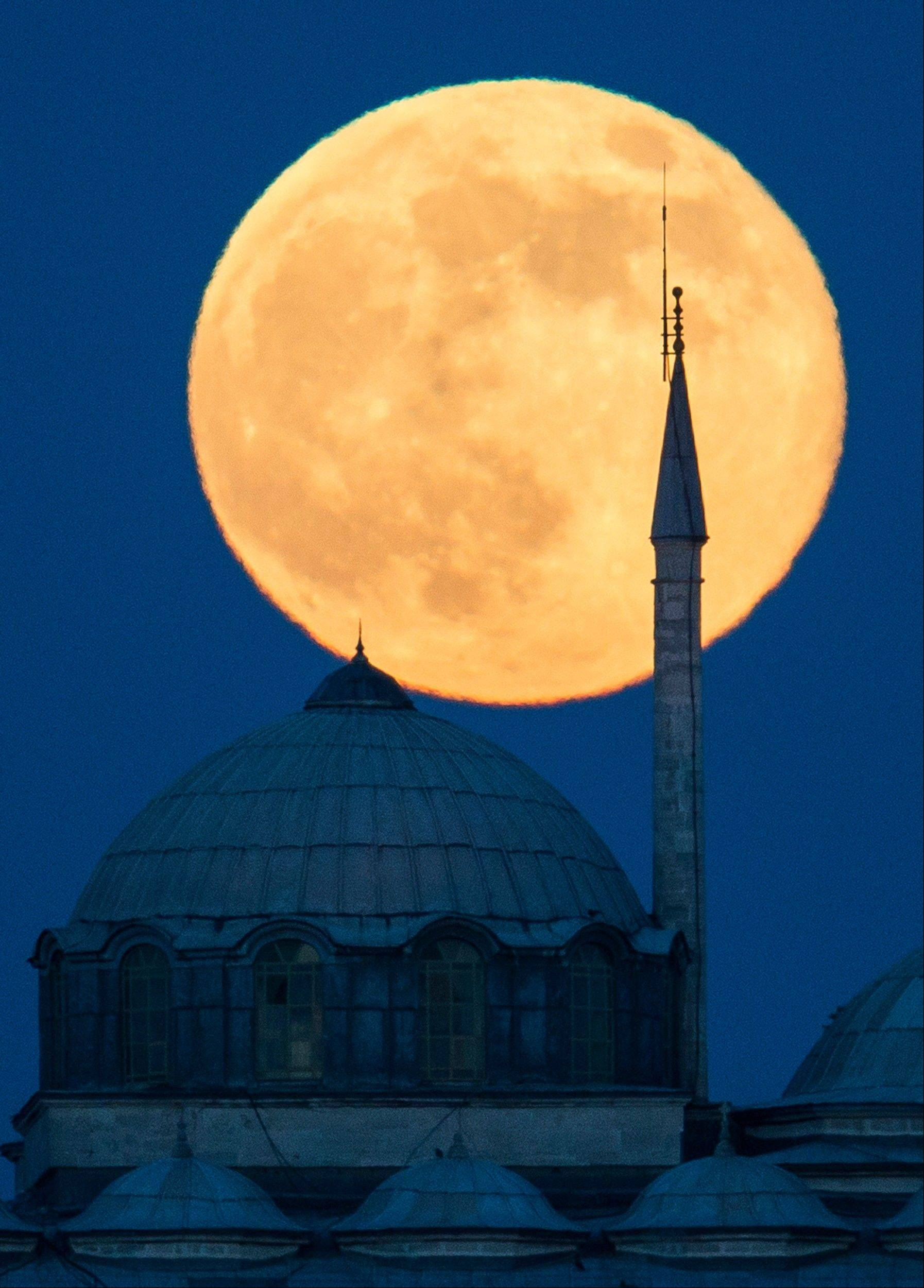"A supermoon rises behind a building of the Topkapi Palace in Istanbul, Turkey, Sunday, June 23, 2013. The moon, which will reach its full stage on Sunday, is expected to be 13.5 percent closer to earth during a phenomenon known as supermoon. The ""Supermoon"" happens only once this year as the moon on its elliptical orbit is at its closest point to earth."