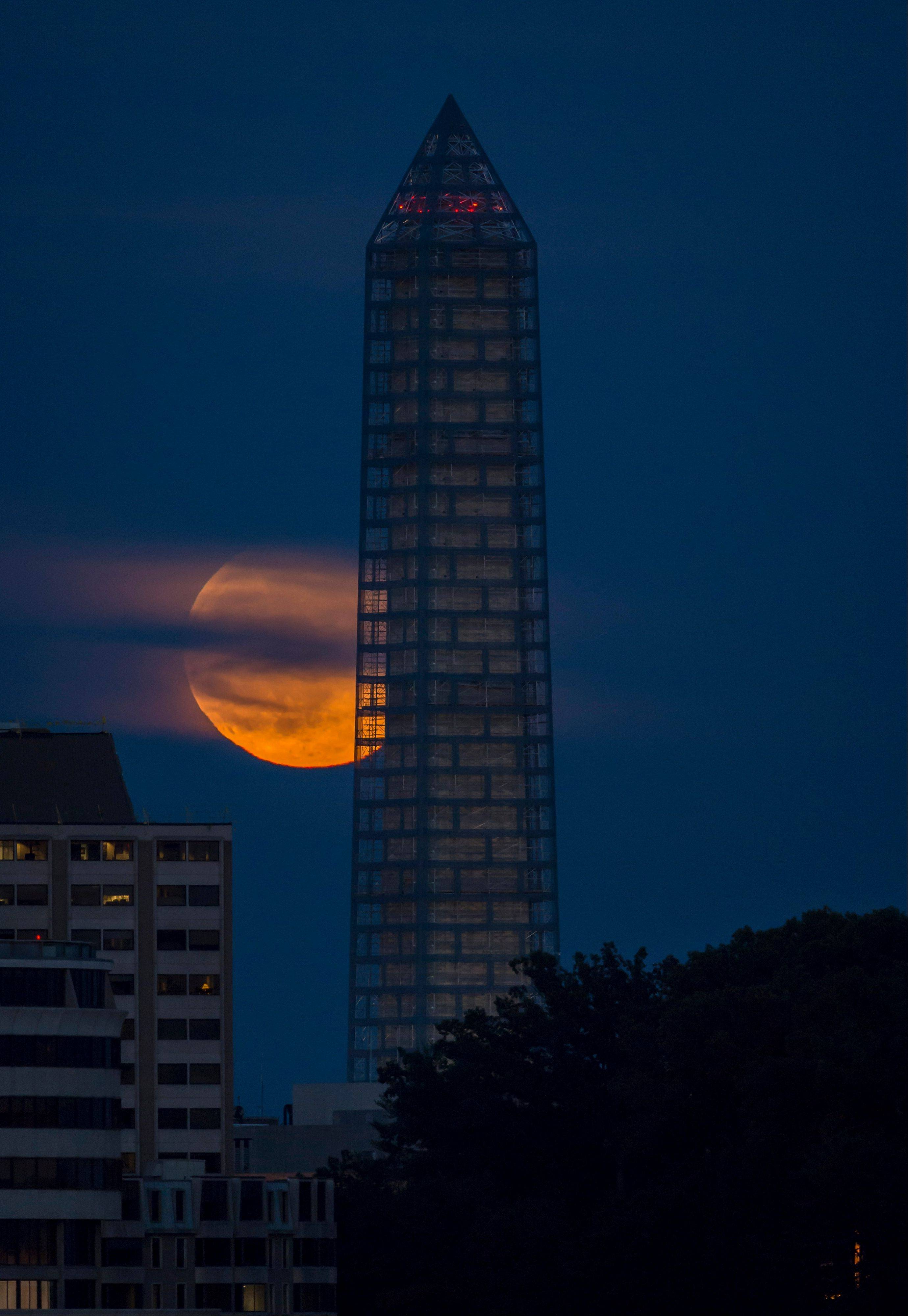 The moon rises behind the Washington Monument, Sunday, June 23, 2013, in Washington. The so-called supermoon appeared up to 14 percent larger than normal as our celestial neighbor swung closer to Earth, reaching its closest distance early Sunday morning.