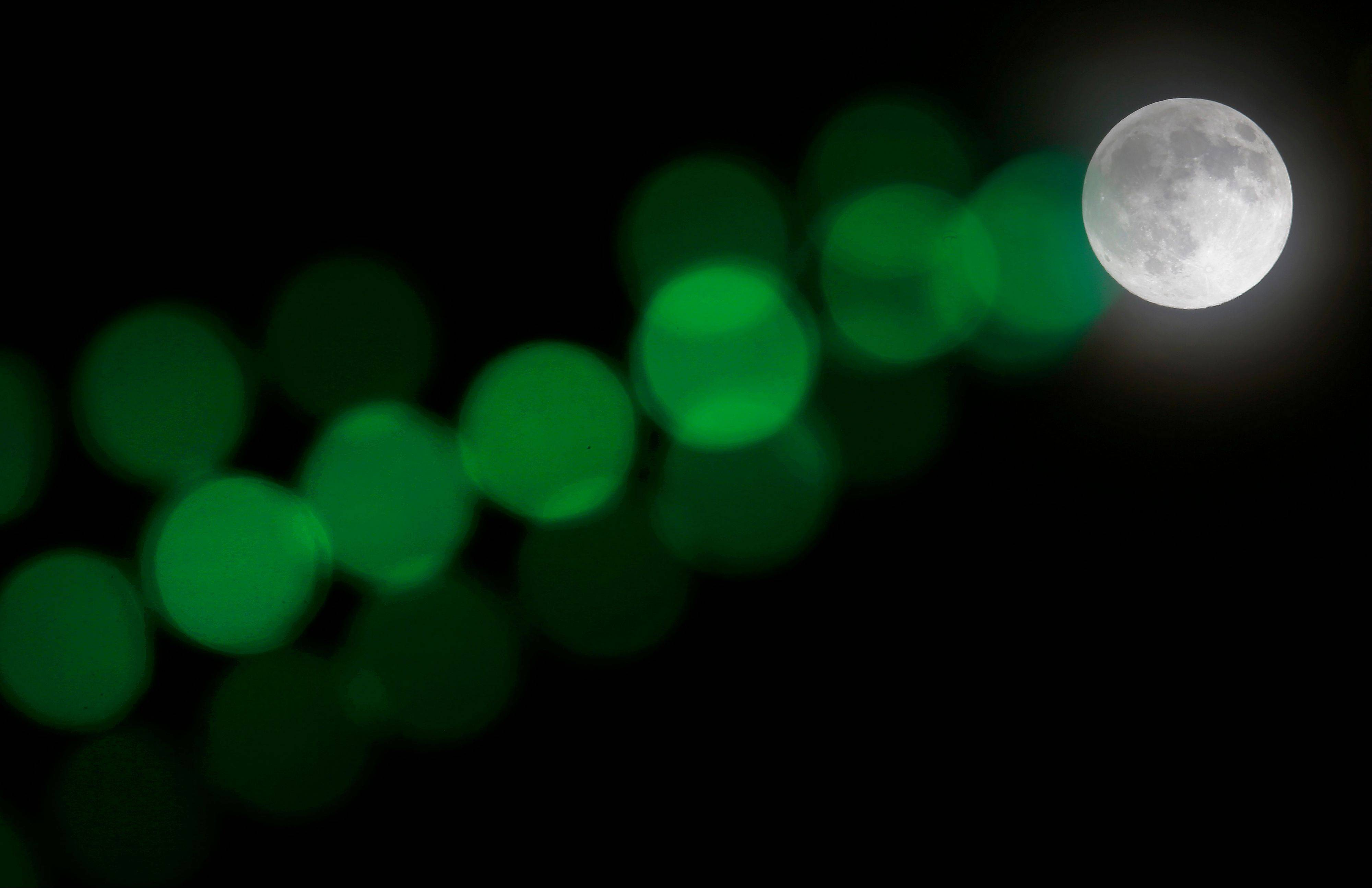 A full moon rises through a hazy sky past a string of green lights, Saturday, June 22, 2013, in Baltimore. The moon, which will reach its full stage on Sunday, is expected to be 13.5 percent closer to earth during a phenomenon known as supermoon.