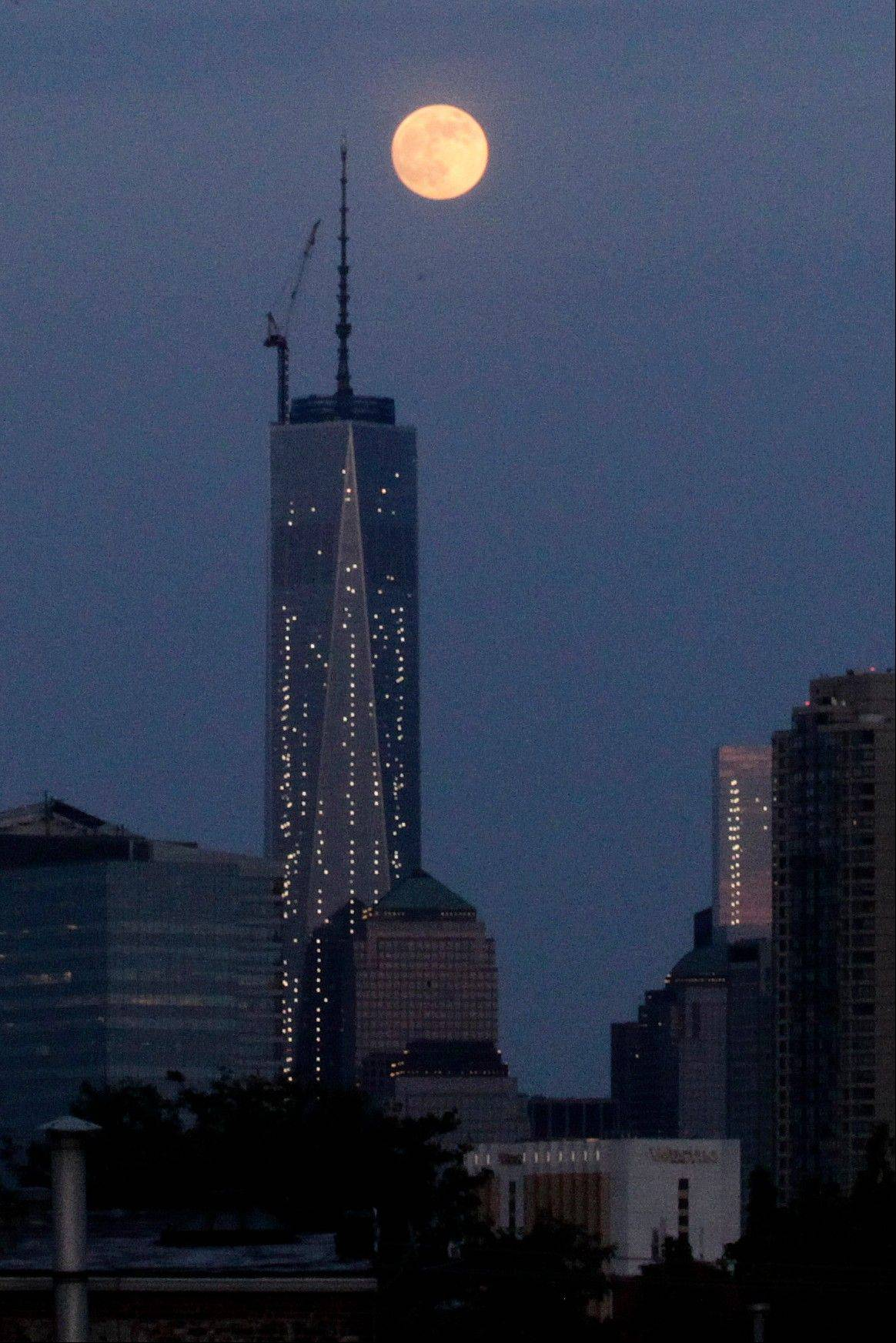 The moon is seen in its waxing gibbous stage as it rises over Lower Manhattan, including One World Trade Center, center, seen from The Heights neighborhood of Jersey City, N.J., Saturday, June 22, 2013. The moon, which will reach its full stage on Sunday, is expected to be seen 13.5 percent larger than usual during a phenomenon known as supermoon.