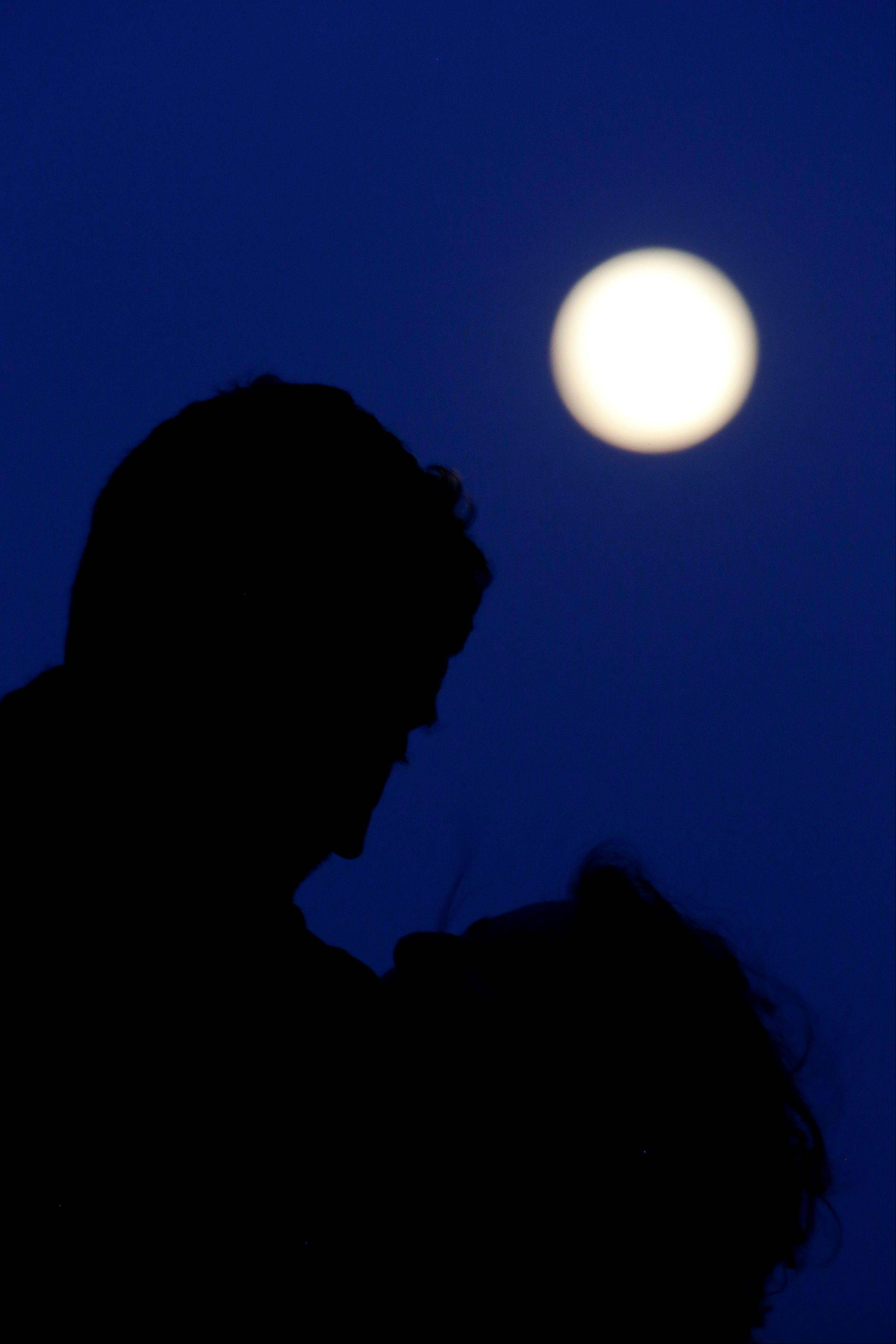 A couple hugs at a Lisbon public garden as the biggest and brightest full moon of the year rises behind them Sunday, June 23 2013. The so-called supermoon appeared up to 14 percent larger than normal as it swung closer to Earth Sunday. (AP Photo/Armando Franca)