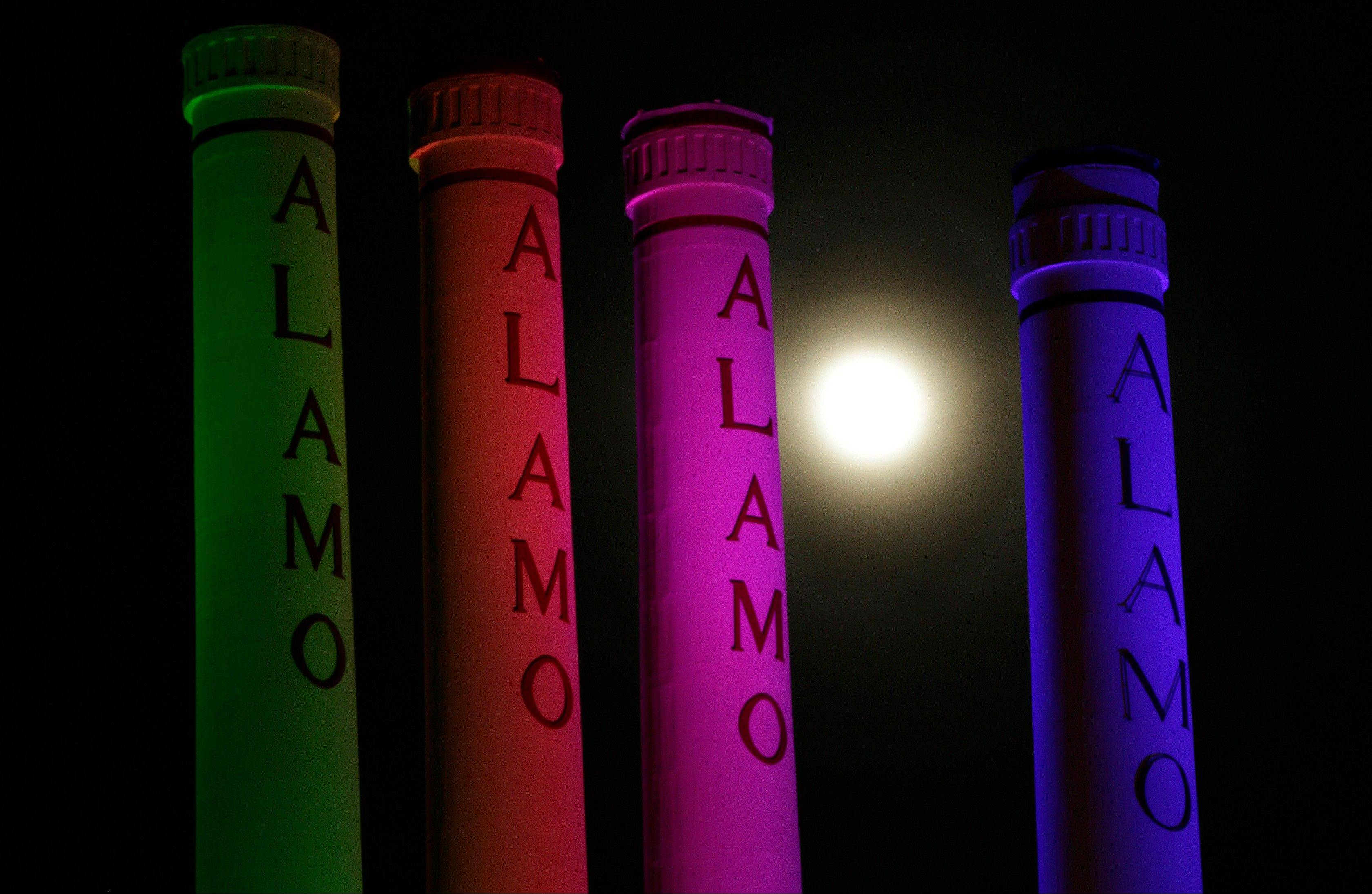 "A hazy ""supermoon"" is seen behind lighted smoke stacks at the Alamo Quarry Markey, formerly a cement factory, Saturday, June 22, 2013, in San Antonio. The biggest and brightest full moon of the year graces the sky early Sunday as our celestial neighbor swings closer to Earth than usual. While the moon will appear larger than normal, sky watchers won't be able to notice the difference with the naked eye."
