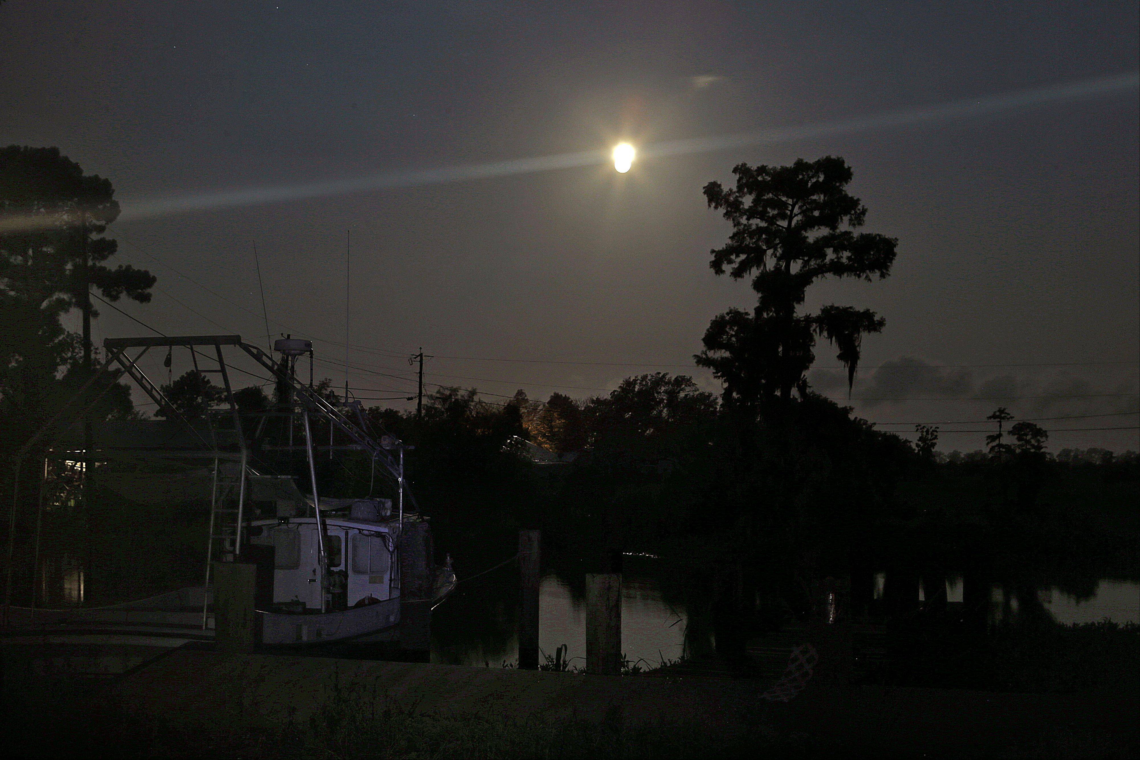 The larger-than-normal full moon referred to as Supermoon is seen setting beyond fishing camps in Akers, La., Sunday, June 23, 2013.