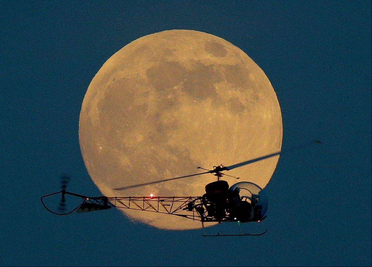 The moon is seen in its waxing gibbous stage as it rises behind the helicopter from the original Batman television show, which people can ride at the New Jersey State Fair, Saturday, June 22, 2013, in East Rutherford, N.J. The moon, which will reach its full stage on Sunday, is expected to be 13.5 percent closer to earth during a phenomenon known as supermoon.