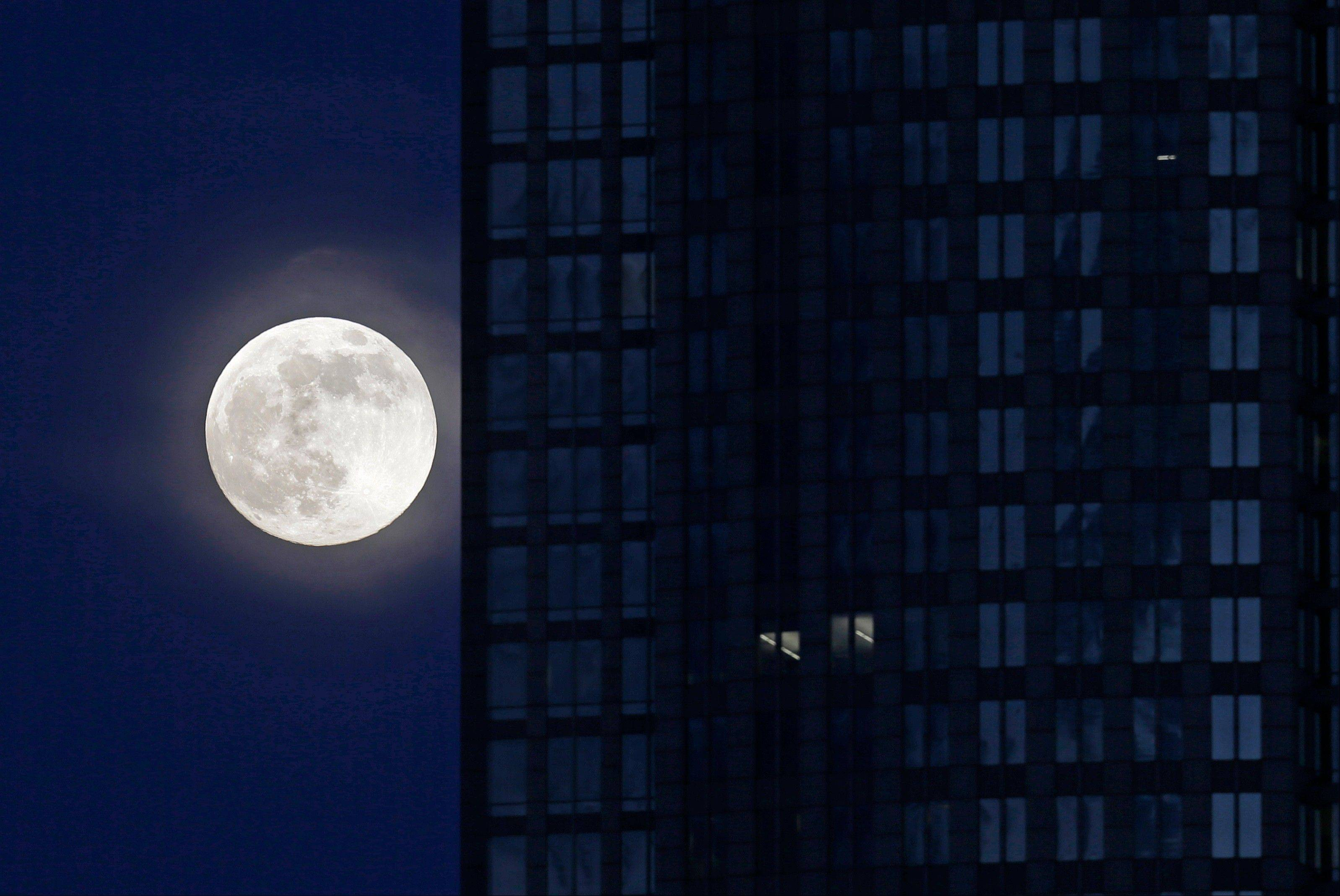 "A full moon rises beside an office building in downtown Charlotte, N.C., Saturday, June 22, 2013. The larger than normal moon called the ""Supermoon"" happens only once this year as the moon on its elliptical orbit is at its closest point to earth."