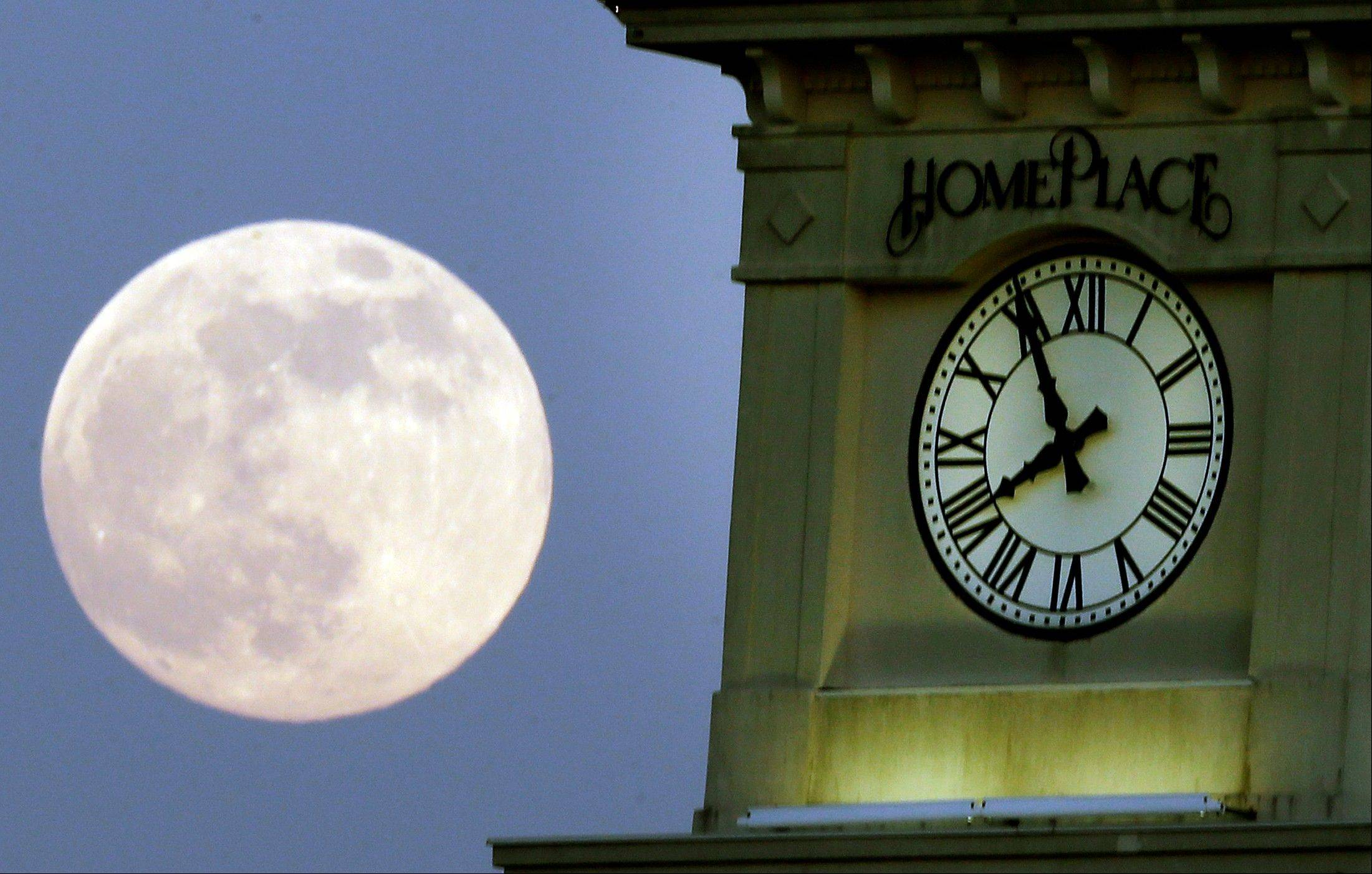 "A ""supermoon"" rises behind the Home Place clock tower in Prattville, Ala., Saturday, June 22, 2013. The biggest and brightest full moon of the year graces the sky early Sunday as our celestial neighbor swings closer to Earth than usual. While the moon will appear 14 percent larger than normal, sky watchers won't be able to notice the difference with the naked eye. Still, astronomers say it's worth looking up and appreciating the cosmos."