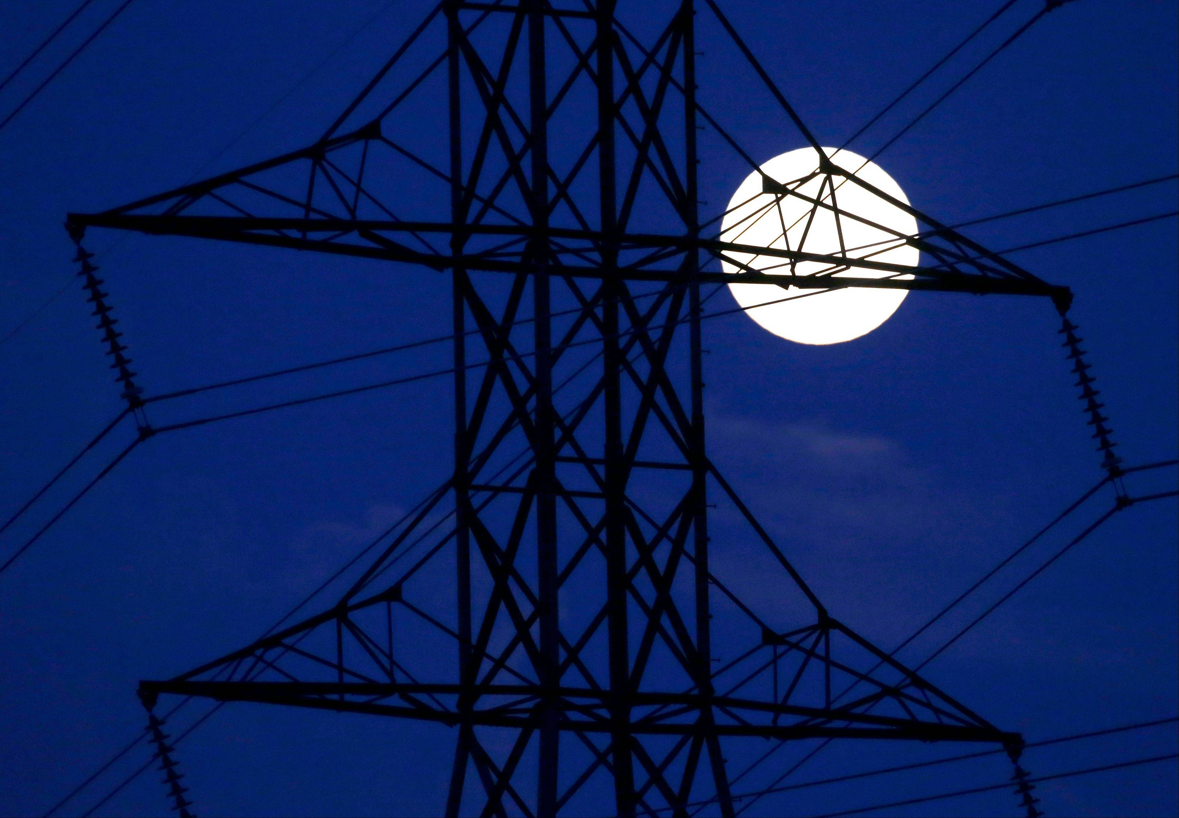 The moon rises behind power lines on Saturday, June 22, 2013, in Nashville, Tenn. The biggest and brightest full moon of the year, called a supermoon, happens as the moon passes closer to earth than usual. Associated Press