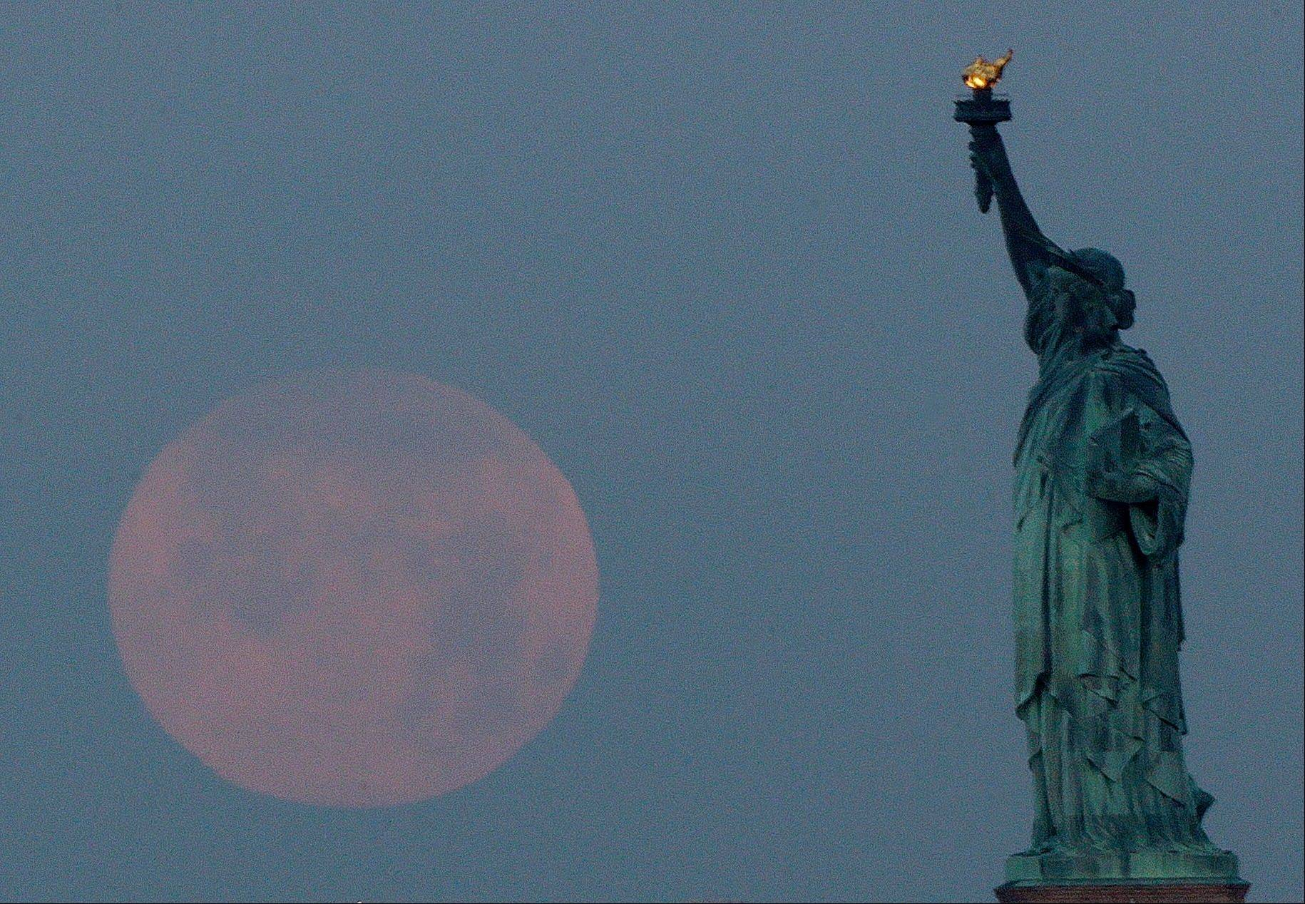 "A supermoon sets near the Statue of Liberty, Sunday, June 23, 2013, in New York. The larger than normal moon called the ""Supermoon"" happens only once this year as the moon on its elliptical orbit is at its closest point to earth and is 13.5 percent larger than usual."
