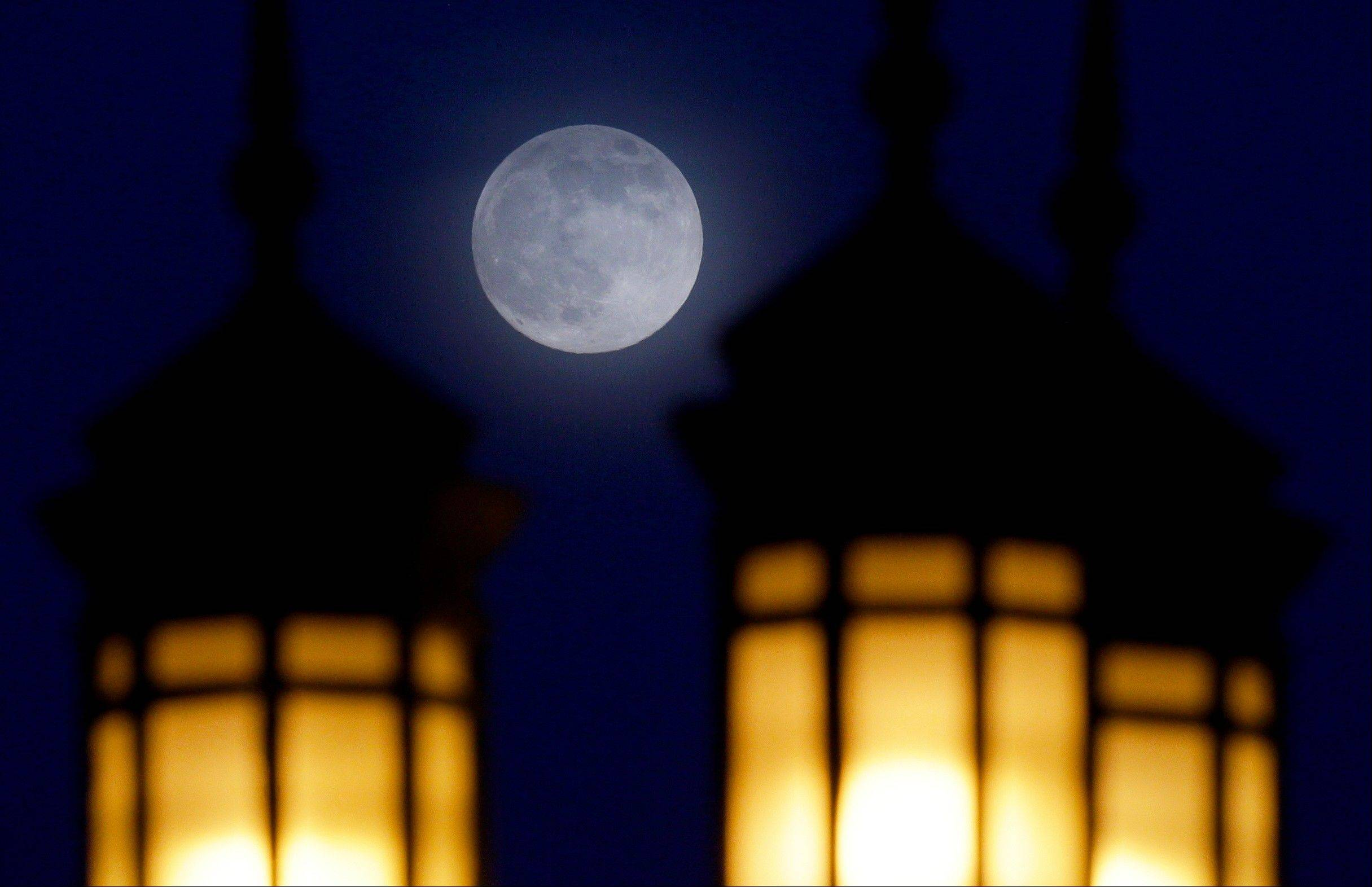 A full moon rises through a hazy sky over street lamps, Saturday, June 22, 2013, in Baltimore. The moon, which will reach its full stage on Sunday, is expected to be 13.5 percent closer to earth during a phenomenon known as supermoon.