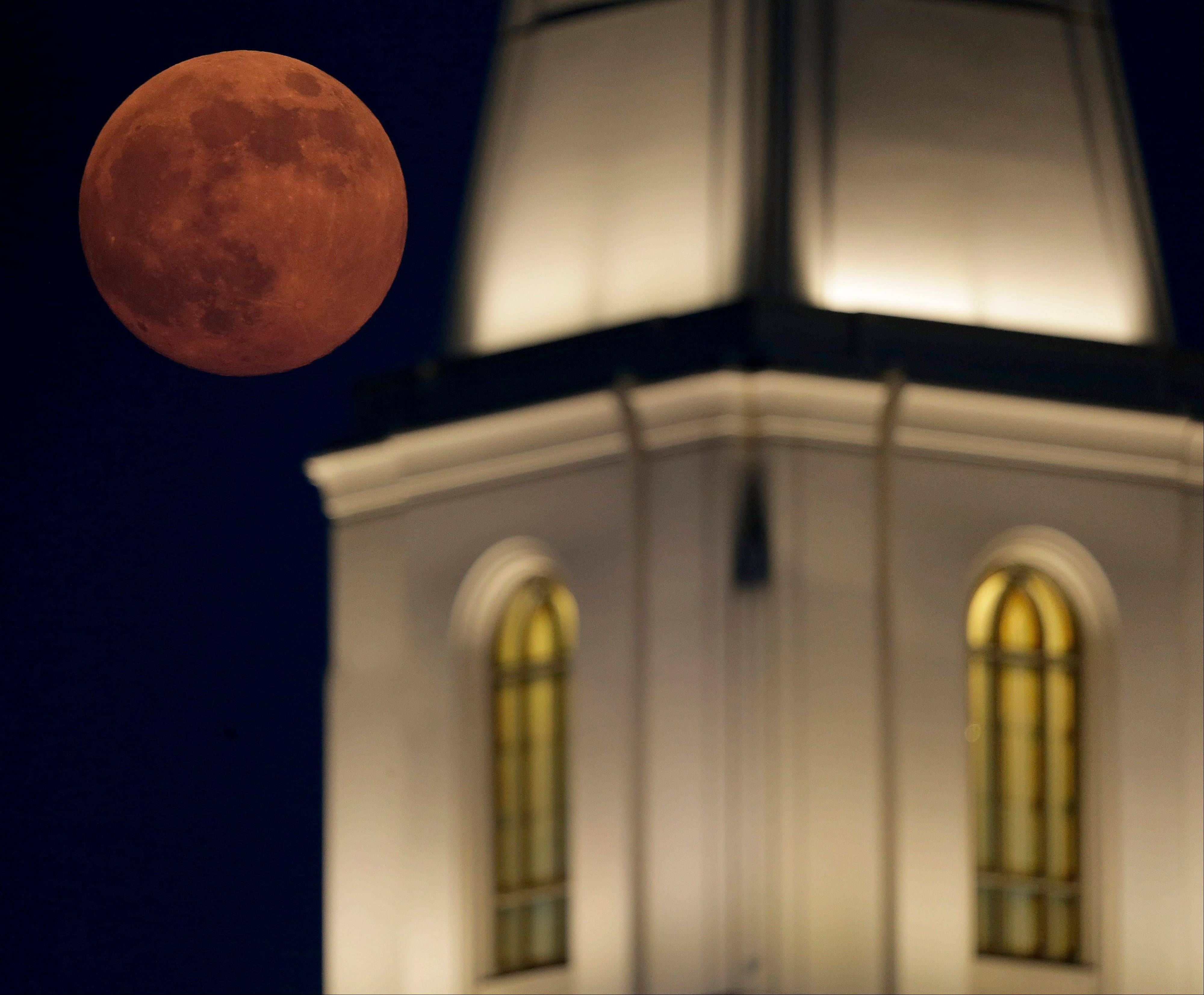 A full moon rises beyond a Latter-day Saints temple Saturday, June 22, 2013, in Kansas City, Mo. The moon, which will reach its full stage on Sunday, is expected to be 13.5 percent closer to earth during a phenomenon known as supermoon.