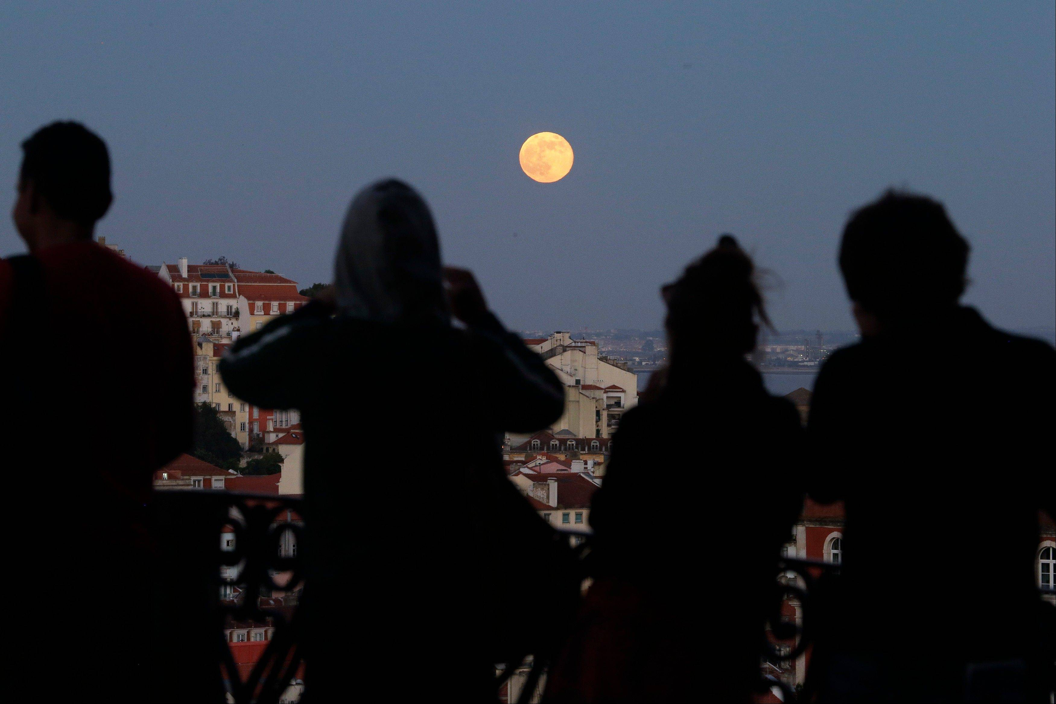 People look at the biggest and brightest full moon of the year rise at a public garden in Lisbon, Portugal Sunday, June 23 2013. The so-called supermoon appeared up to 14 percent larger than normal as it swung closer to Earth Sunday.