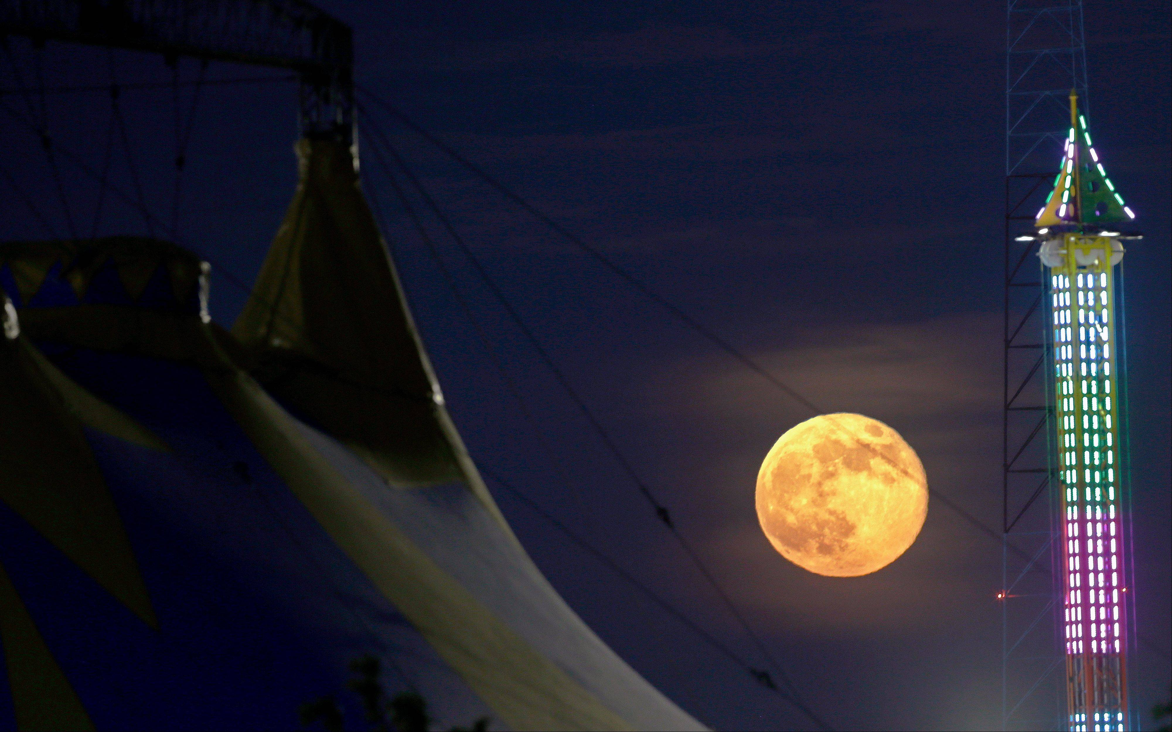 The moon rises between a tent, left, and a ride at State Fair Meadowlands, Sunday, June 23, 2013, in East Rutherford, N.J. The so-called supermoon appeared up to 14 percent larger than normal this weekend as our celestial neighbor swung closer to Earth, reaching its closest distance early Sunday morning.