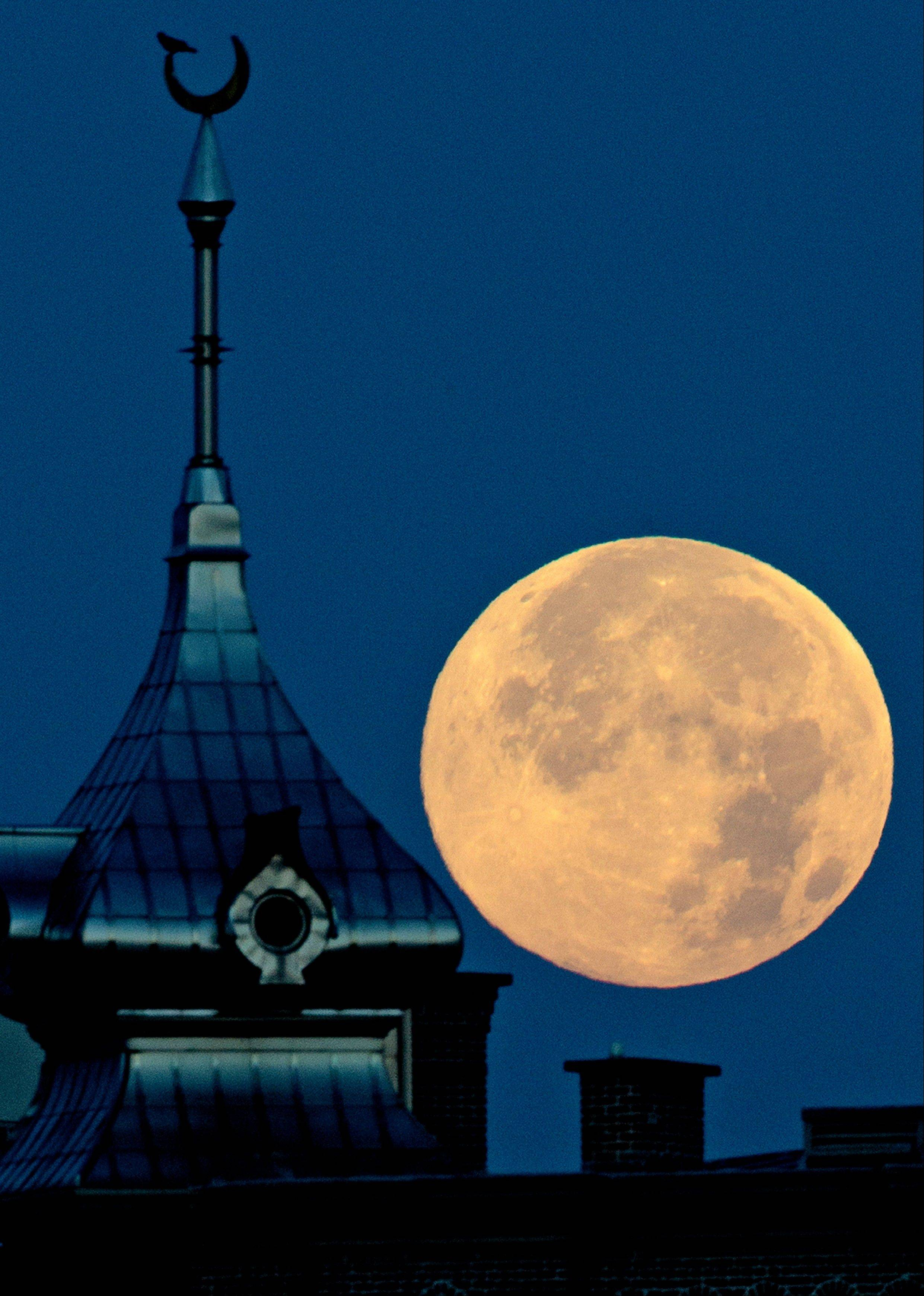 A full super moon sets behind the top of one of the minarets at the University of Tampa Sunday, June 23, 2013, in Tampa, Fla.