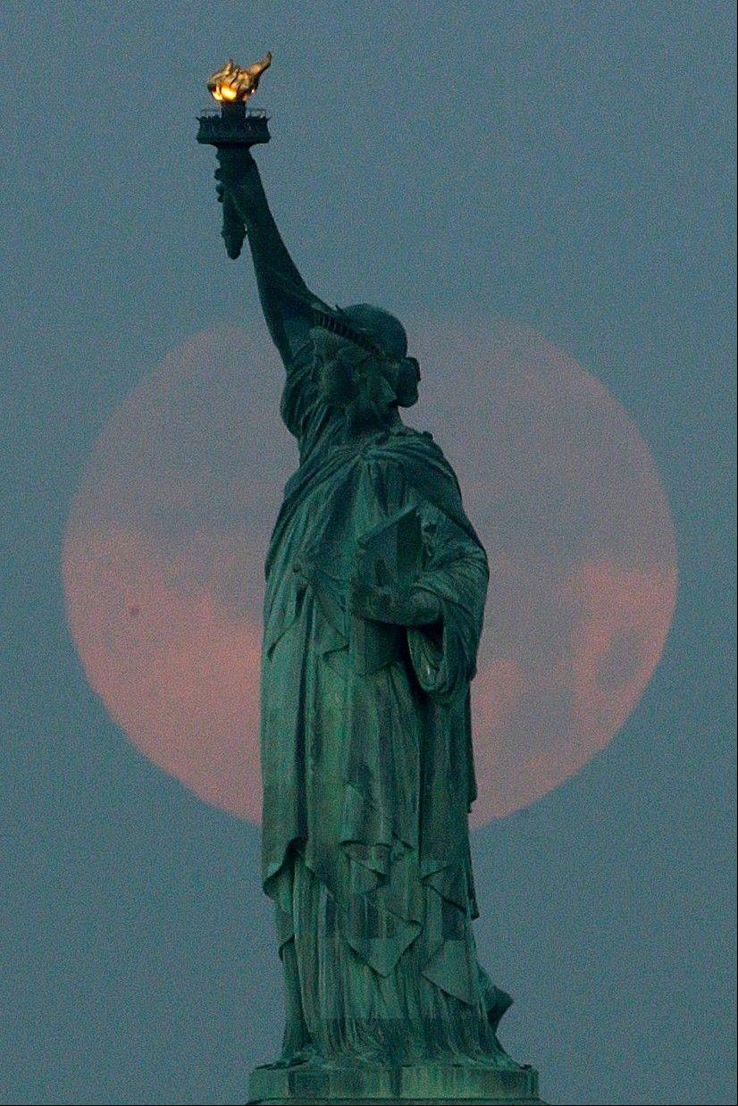 "A supermoon sets behind the Statue of Liberty, Sunday, June 23, 2013, in New York. The larger than normal moon called the ""Supermoon"" happens only once this year as the moon on its elliptical orbit is at its closest point to earth and is 13.5 percent larger than usual."
