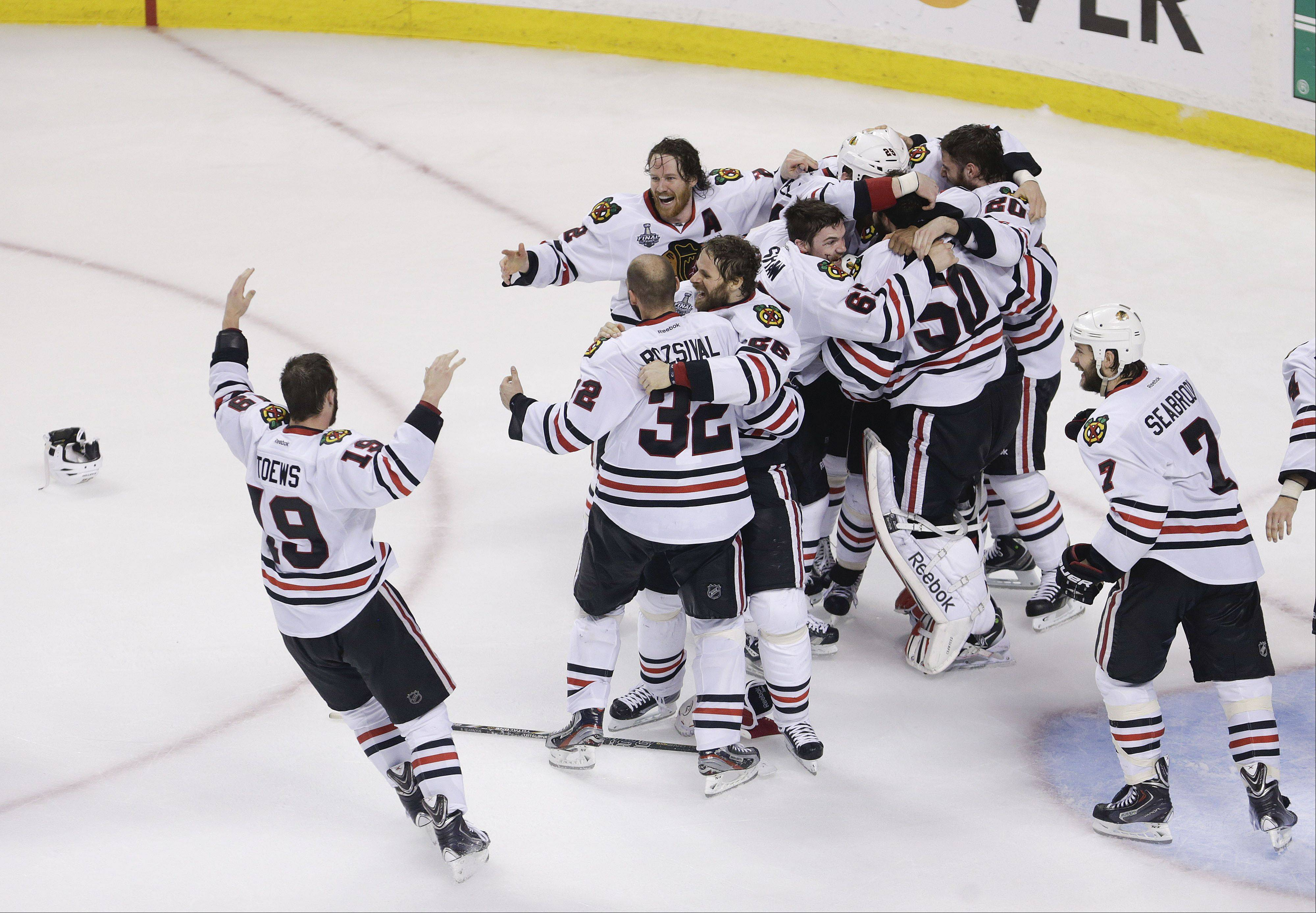 The Blackhawks celebrate their 3-2 win over the Boston Bruins Monday in Game 6 of the Stanley Cup Finals in Boston. The Hawks won the series 4-2.