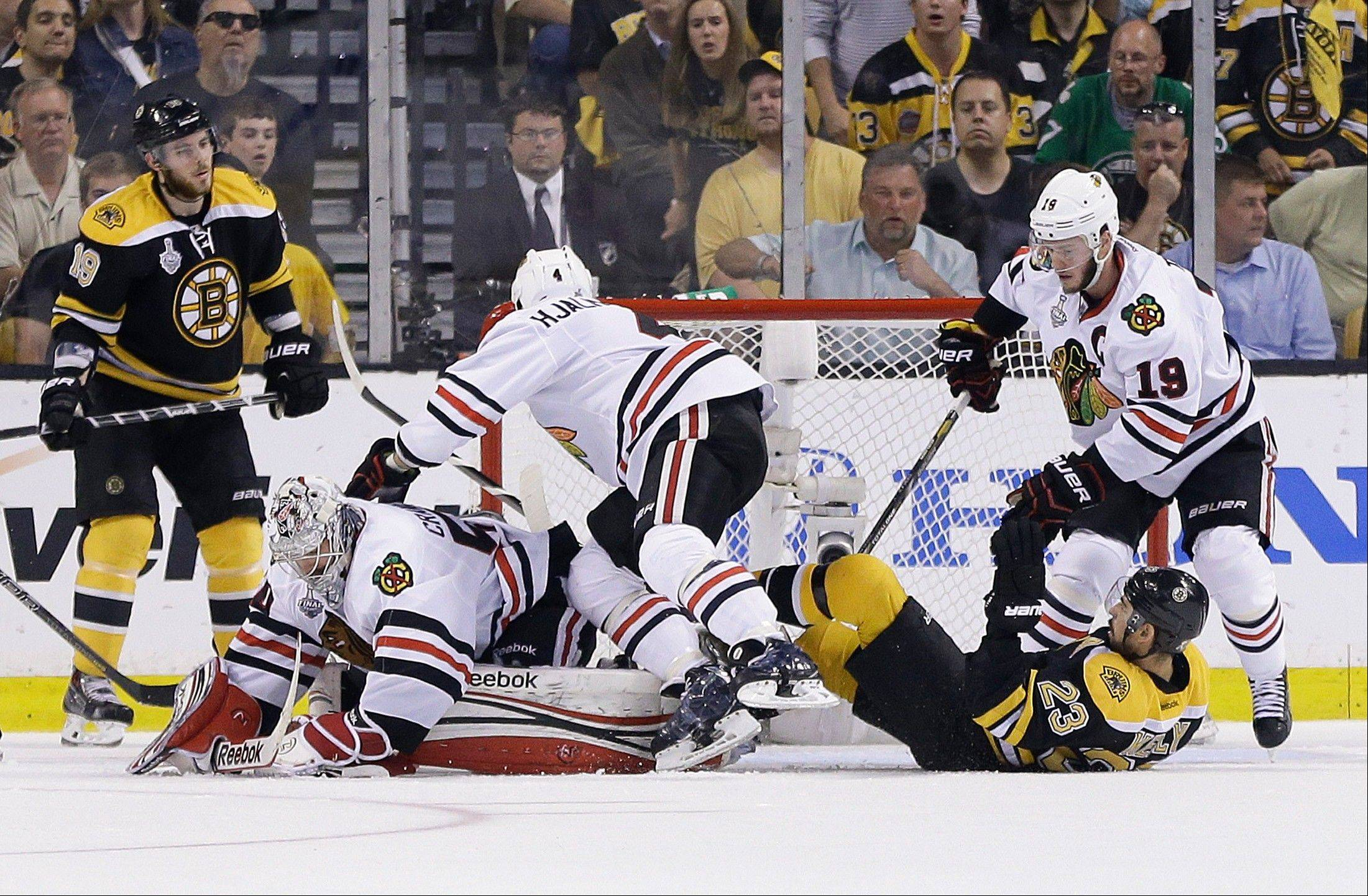 Blackhawks defenseman Niklas Hjalmarsson Boston Bruins center Chris Kelly (23) go down between Blackhawks goalie Corey Crawford, left, and Blackhawks center Jonathan Toews, right, during the first period Monday in Game 6 in Boston. \
