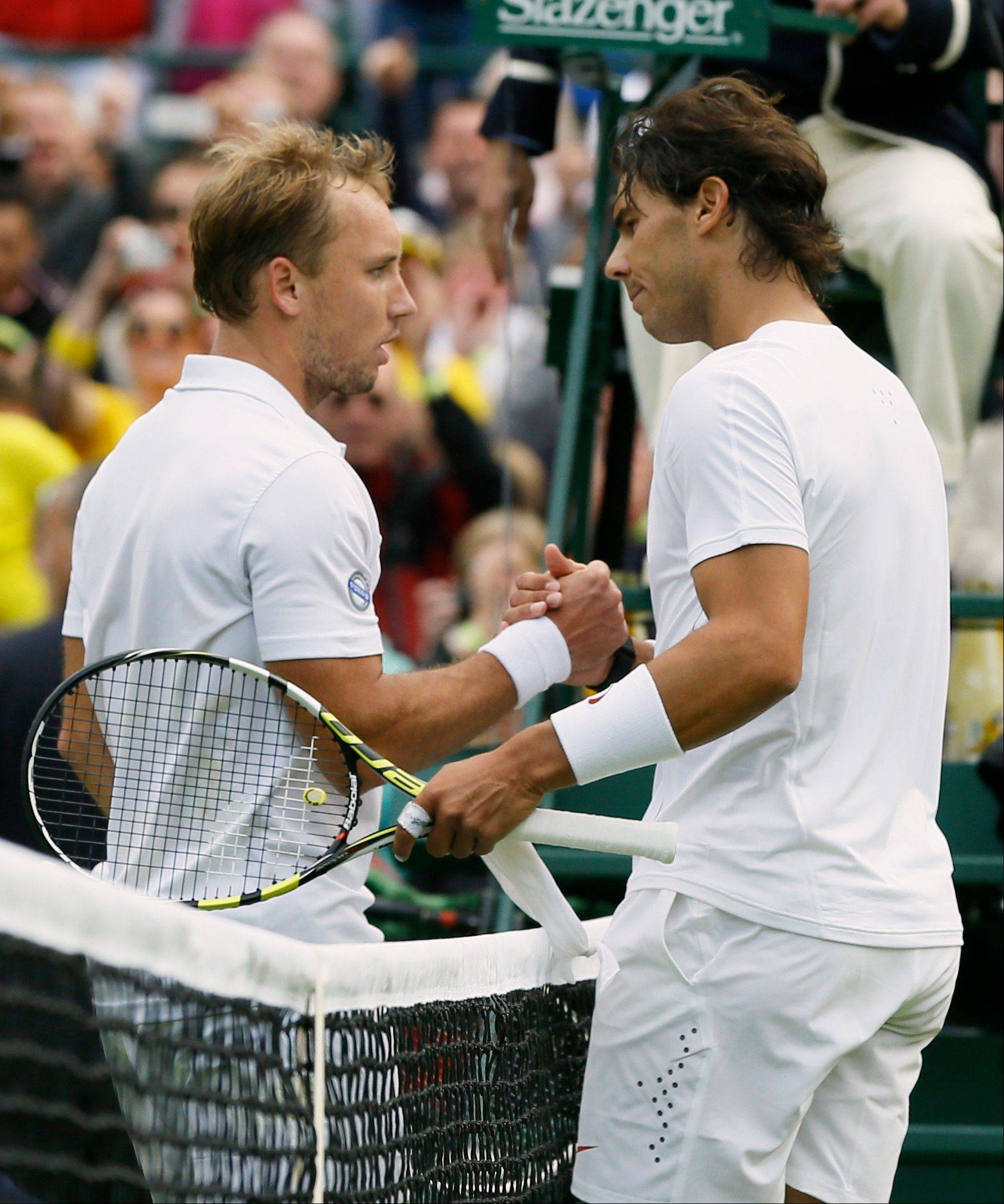 Rafael Nadal shakes hands with Steve Darcis Monday after he lost in their first round singles match at the All England Lawn Tennis Championships in Wimbledon.