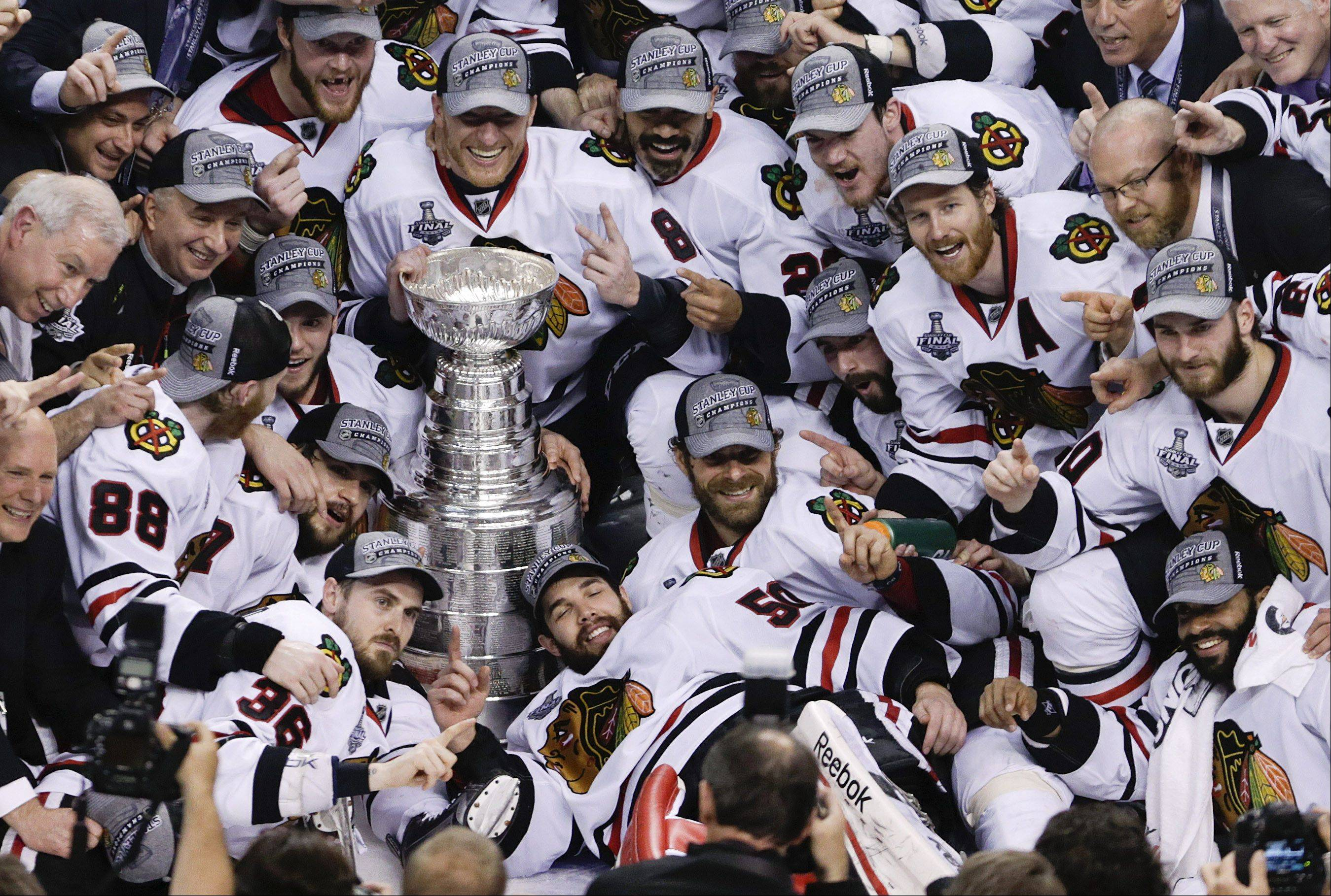 The Blackhawks pose with the Stanley Cup after beating the Boston Bruins 3-2 in Game 6 of the NHL hockey Stanley Cup Finals, Monday, June 24, 2013, in Boston.