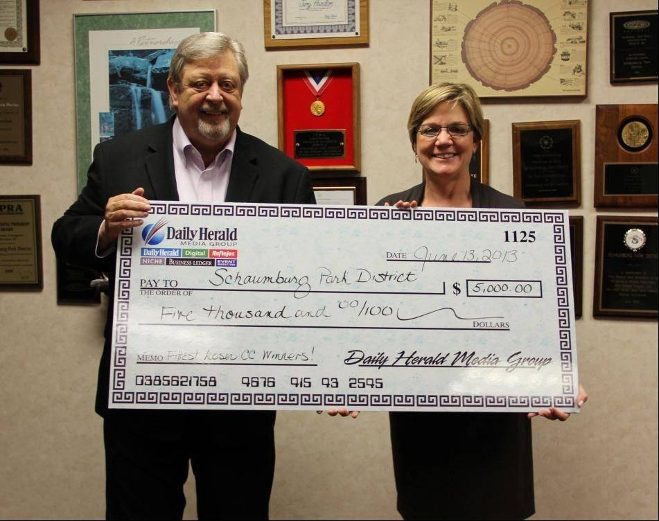 Park Board President Mike Daniels accepts a $5,000 check from Eileen Brown, director of innovation and audience development for the Daily Herald, for the Park District's Waist Management team winning the Fittest Loser Community Challenge.
