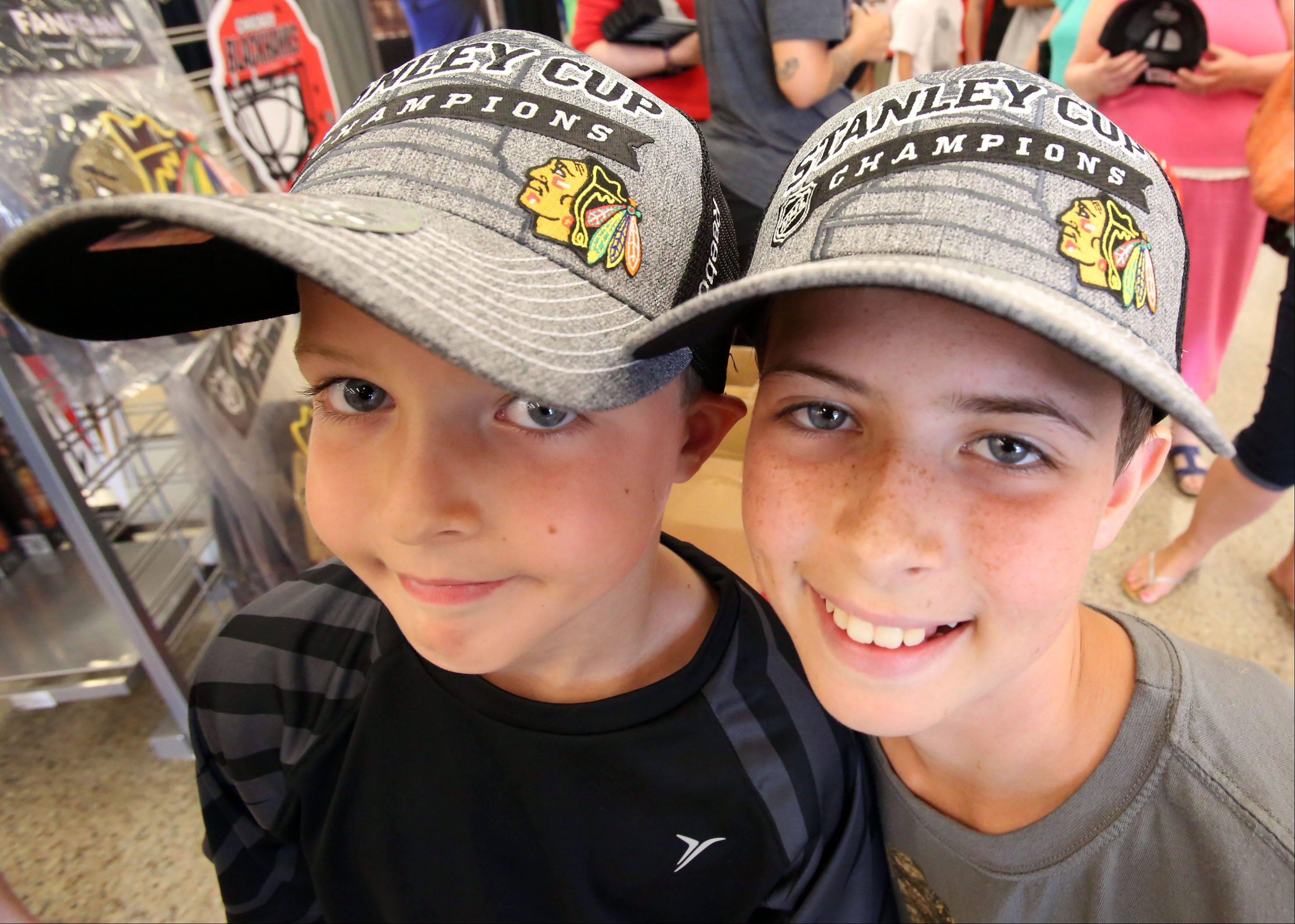 Even though they waited two hours in line, Patrick Tinsley, 7, left, and his brother Jack, 12, of Arlington Heights, are all smiles after getting their official Chicago Blackhawks Stanley Cup hats on Tuesday at Sports Authority in Mount Prospect.