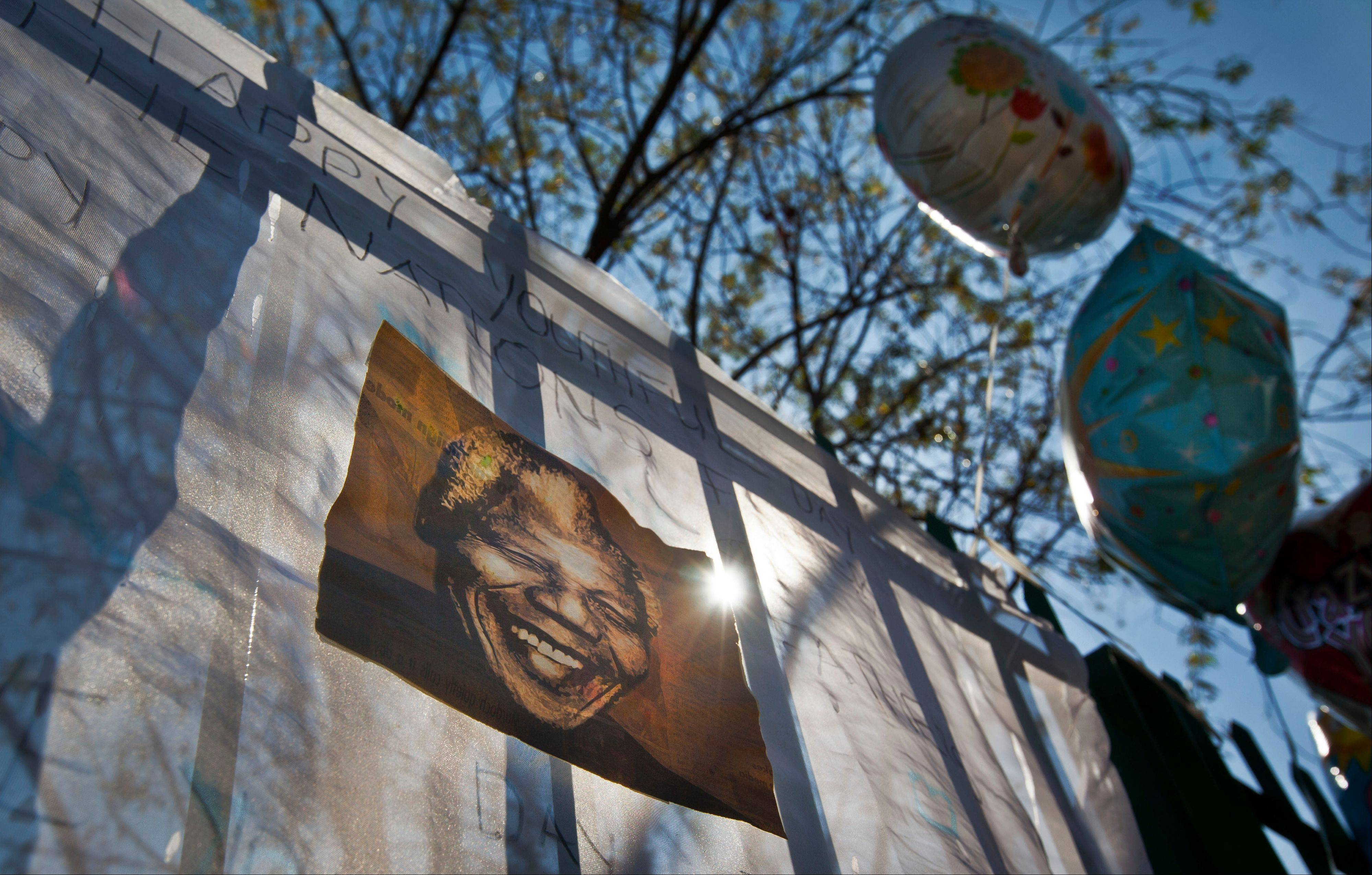 A get-well message carrying a photo of Nelson Mandela hangs on the railings at the entrance to the Mediclinic Heart Hospital where the former South African President is being treated in Pretoria, South Africa Tuesday, June 25, 2013. South Africans passed by Nelson Mandela�s home in a Johannesburg suburb on Tuesday and said they were praying for the 94-year-old after the President Jacob Zuma urged the country to send their wishes to the man he called the �father of democracy,� who remained in critical condition.