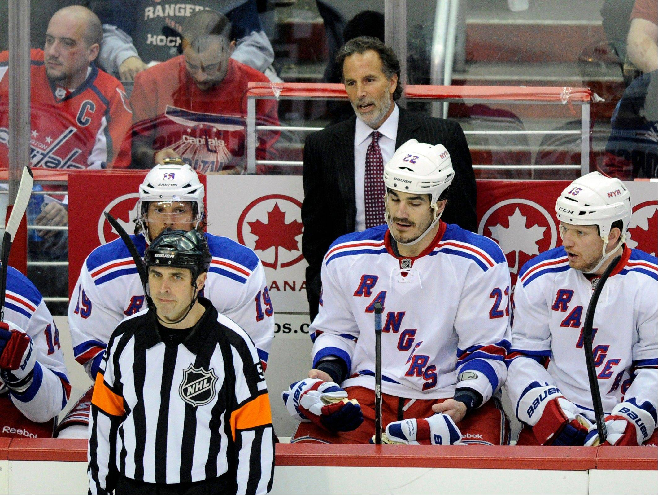 FILE - In this May 13, 2013, file photo, New York Rangers head coach John Tortorella, top rear, looks on from behind the bench during the second period of Game 7 first-round NHL Stanley Cup playoff hockey series against the Washington Capitals in Washington. The Vancouver Canucks hired Tortorella to be their new coach on Tuesday, June 25, 2013. Tortorella was recently fired by the Rangers after they lost to the Boston Bruins in the playoffs in five games. (AP Photo/Nick Wass, File)