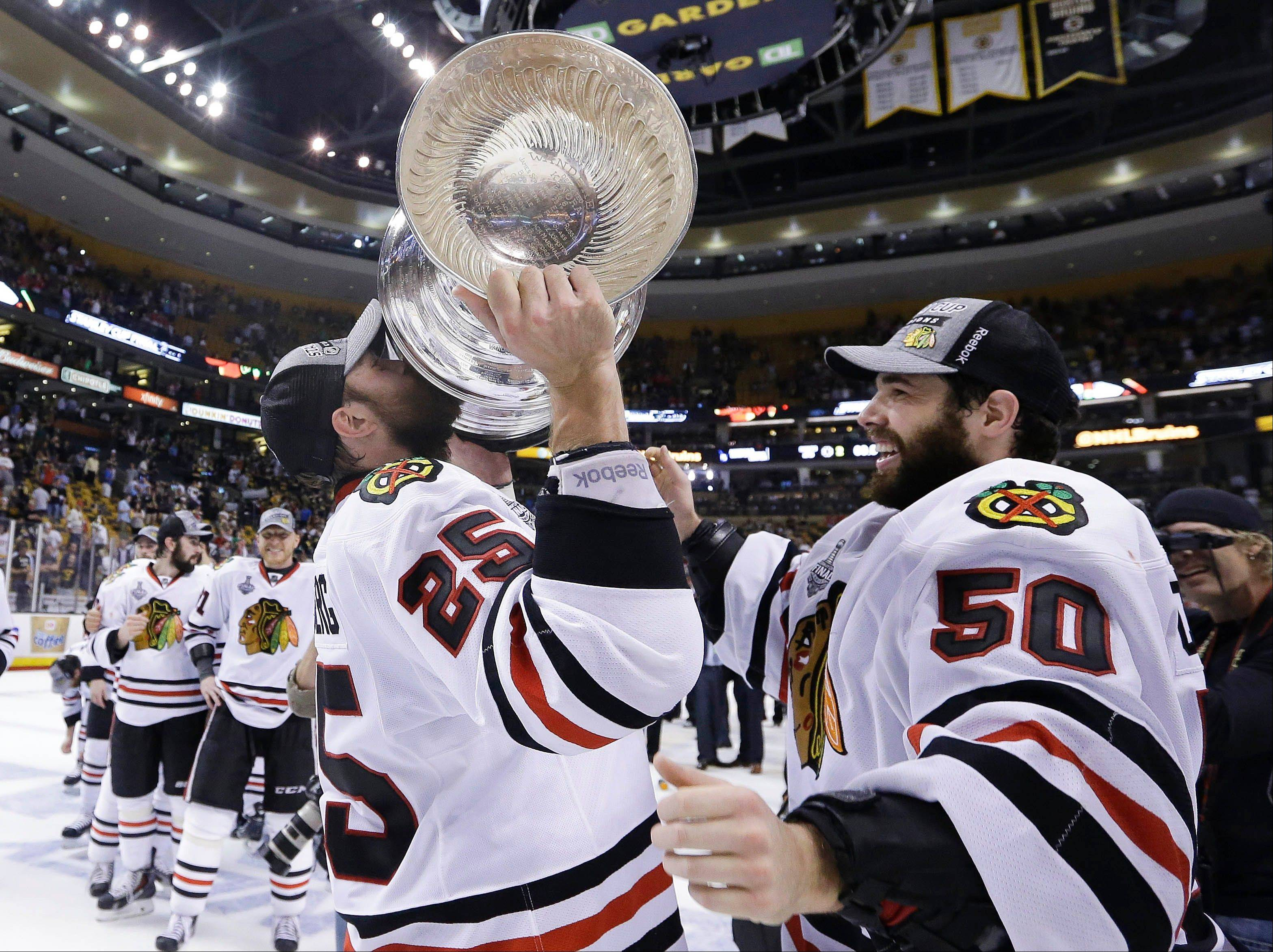 Chicago Blackhawks left wing Viktor Stalberg (25), of Sweden, hoists the Stanley Cup alongside goalie Corey Crawford (50) after the Blackhawks beat the Boston Bruins in Game 6 of the NHL hockey Stanley Cup Finals Monday in Boston.