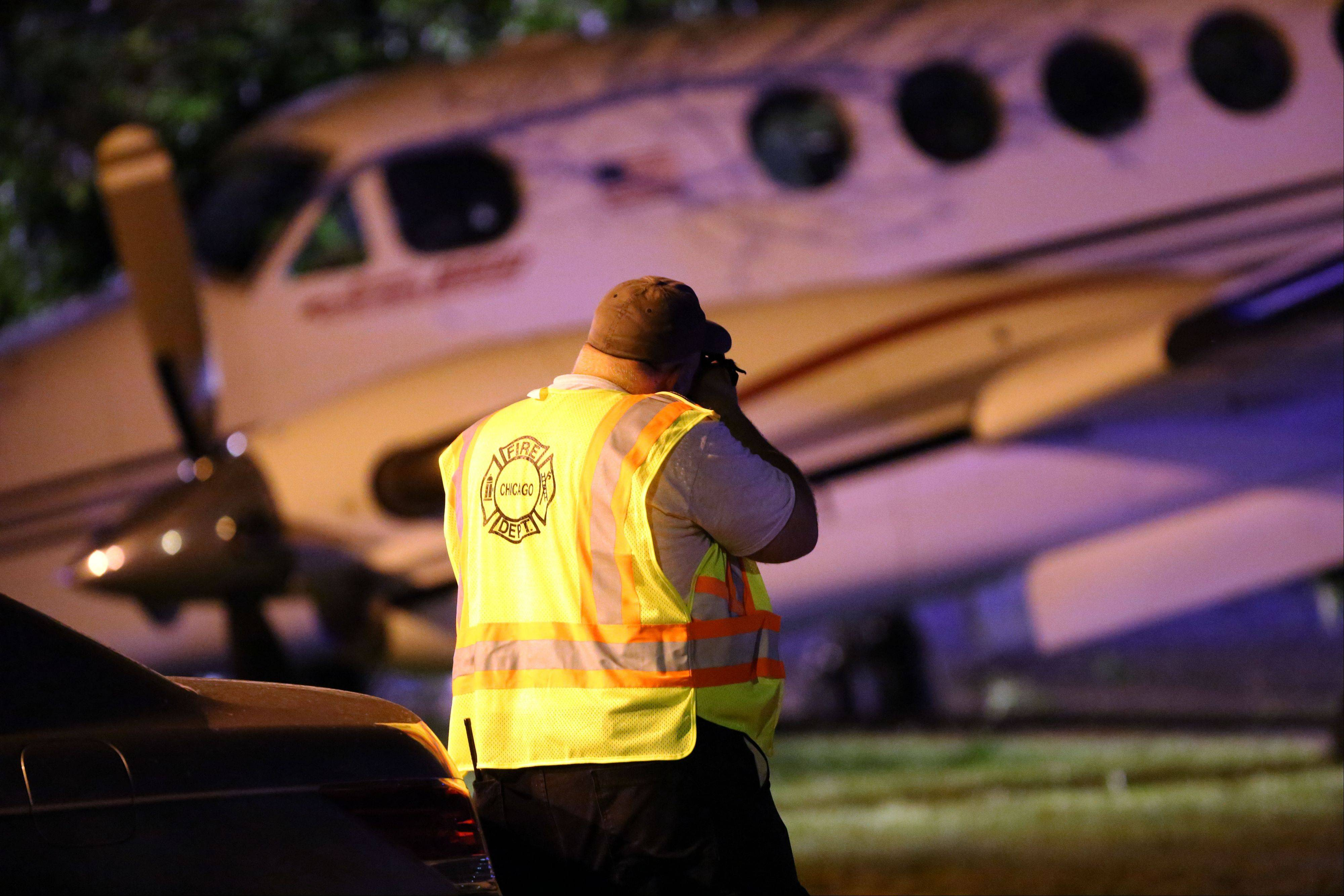 An investigator shoots pictures of a plane that crashed Tuesday on Wolf Road in Wheeling near the Foxboro Apartments.