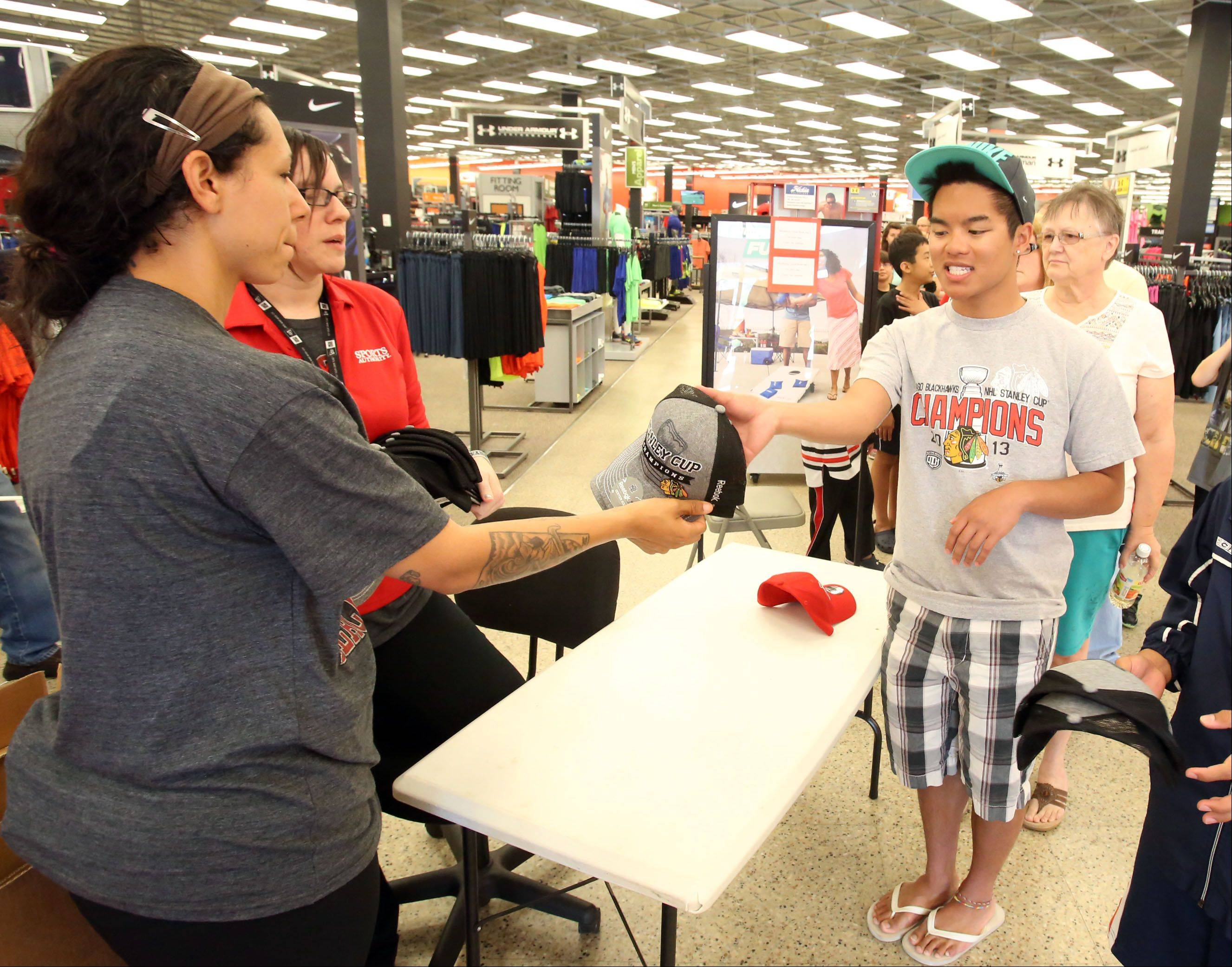 After waiting in line for two hours for a new shipment to arrive, Jeremy Vivit of Mount Prospect gets one of the last official Chicago Blackhawks Stanley Cup hats from Tanya Neitzke at Sports Authority in Mount Prospect on Tuesday.