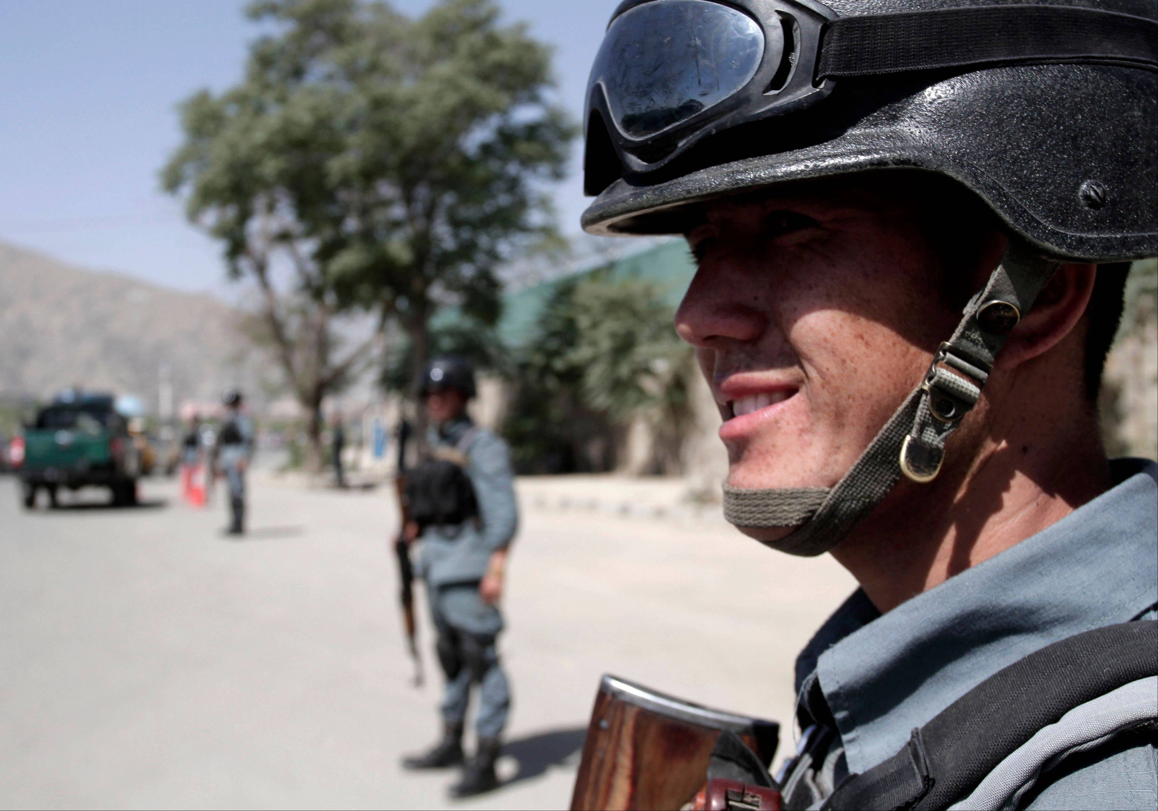 Afghan security forces stand guard near the entrance gate of the presidential palace in Kabul Tuesday. Suicide attackers blew up a car bomb and battled security forces outside the presidential palace Tuesday after infiltrating one of the most secure areas of the capital.