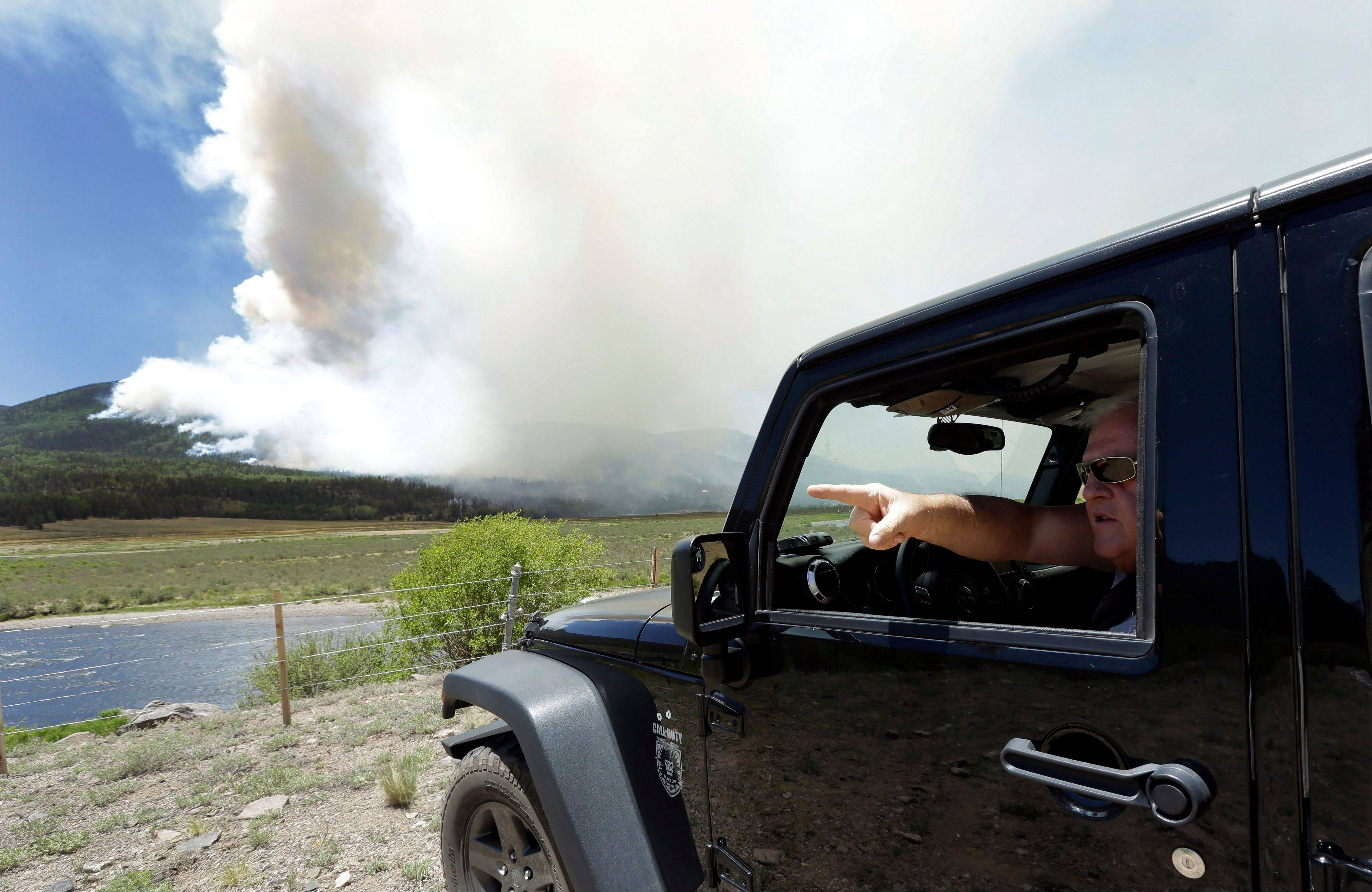 Garry Van Der Starre points out as a wildfire burns on a hillside along highway 149 west of Creede, Colo., Monday, June 24, 2013. Crews defending resort towns, homes and cabins against a massive and erratic wildfire in Colorado's southwest mountains were looking Tuesday for a slight break after nearly a week of unrelenting winds.