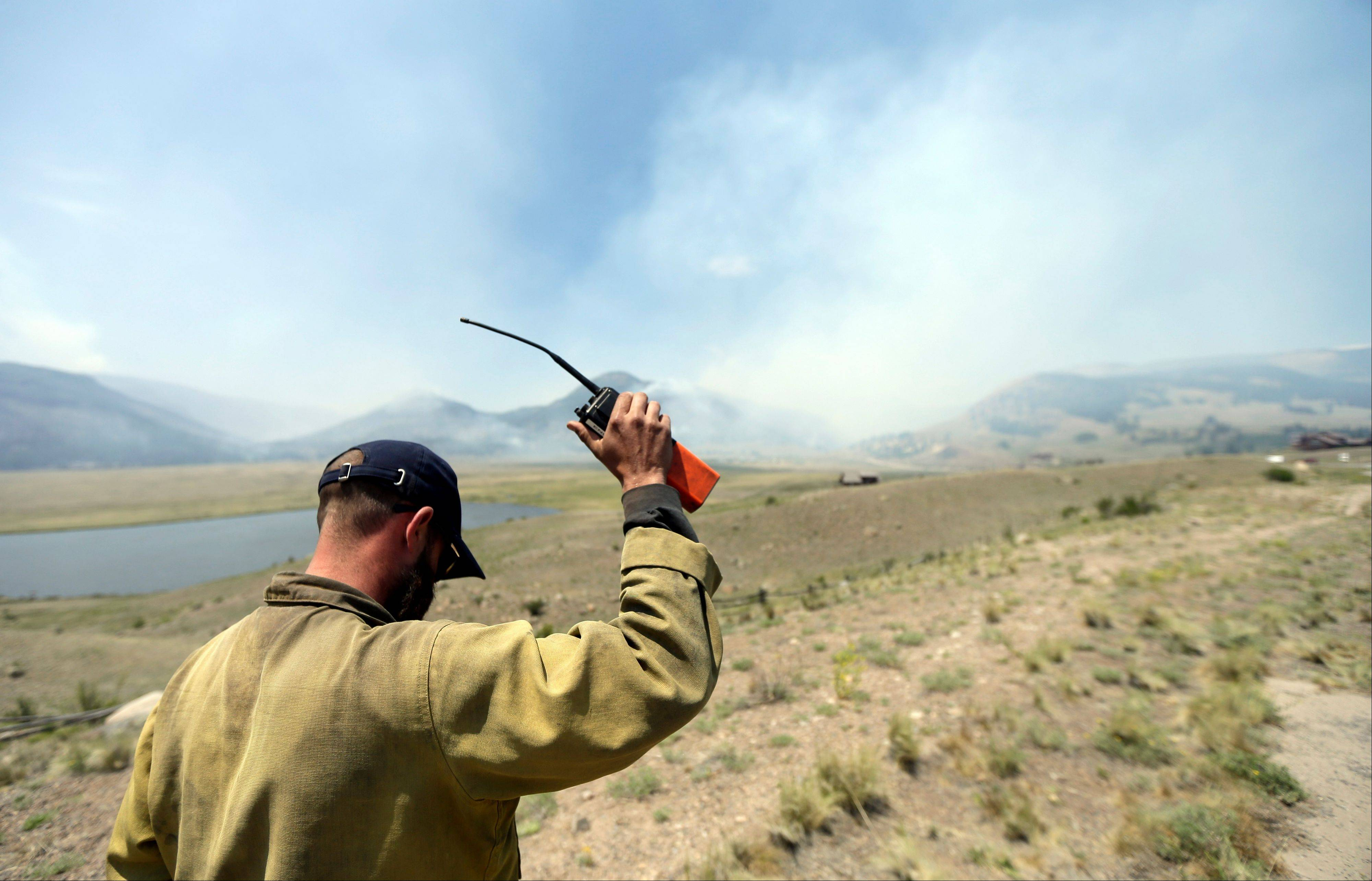Idaho firefighter David Inskee holds his radio in the air for better reception as he keeps an eye on wildfires along highway 149 west of Creede, Colo., Monday, June 24, 2013.