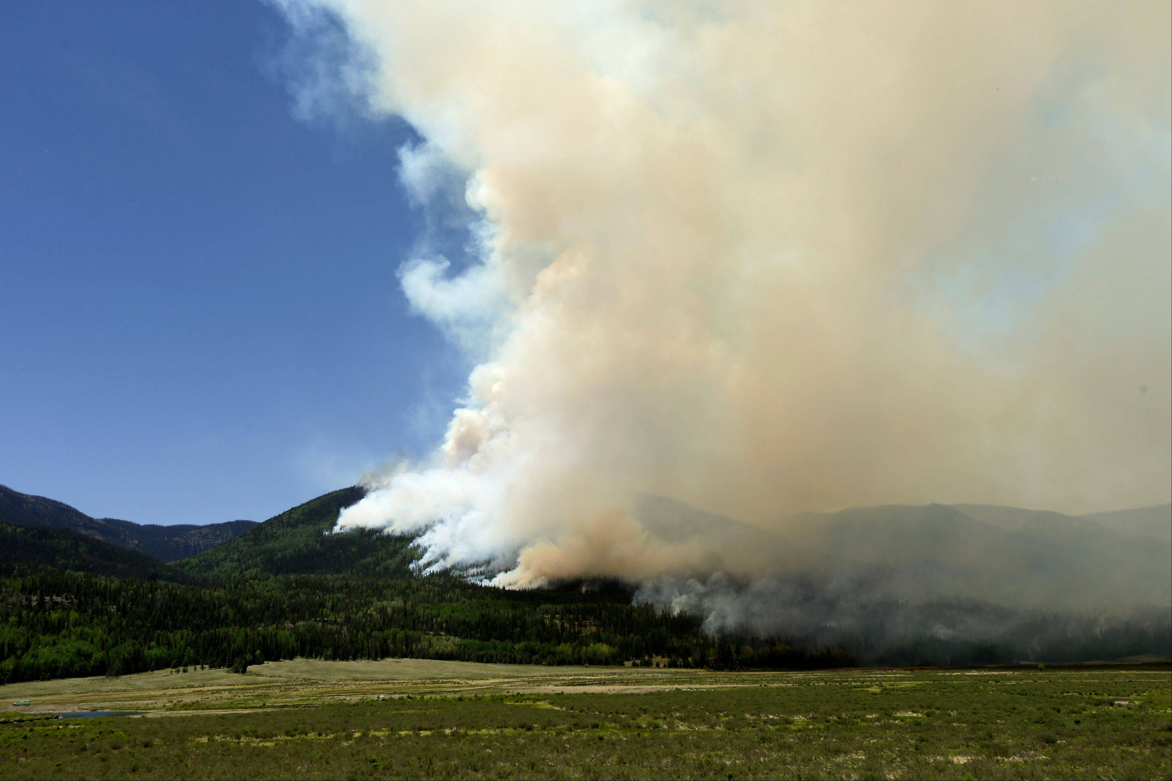A wildfire burns on a hillside along highway 149 west of Creede, Colo., Monday, June 24, 2013. Crews defending resort towns, homes and cabins against a massive and erratic wildfire in Colorado's southwest mountains were looking Tuesday for a slight break after nearly a week of unrelenting winds.