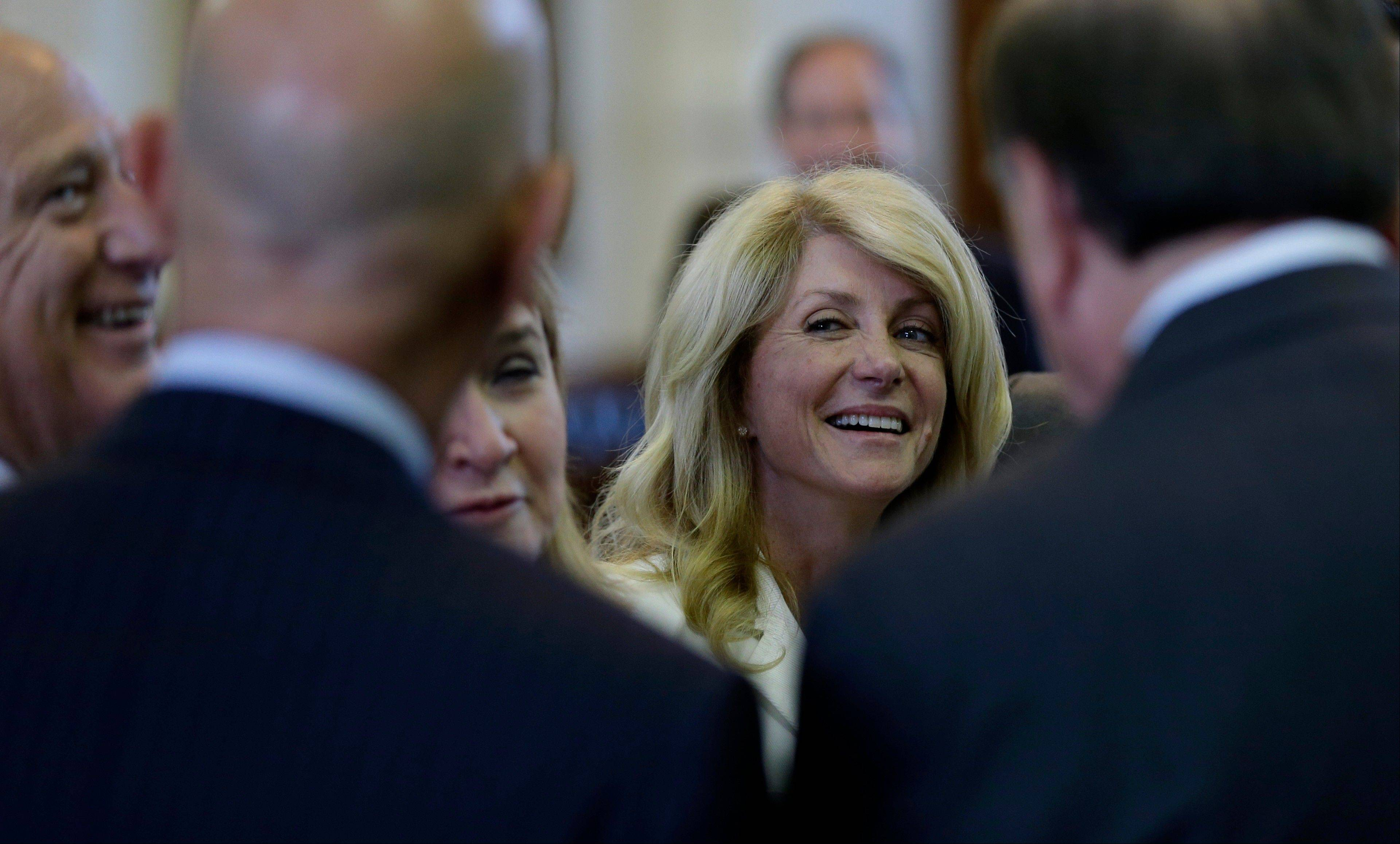 Sen. Wendy Davis, D-Fort Worth, center, talks with fellow senators during a recess, Monday, June 24, 2013, in Austin, Texas. Senate democrats are trying to hold off on a bill that would ban abortion after 20 weeks of pregnancy and force many clinics that perform the procedure to upgrade their facilities and be classified as ambulatory surgical centers.