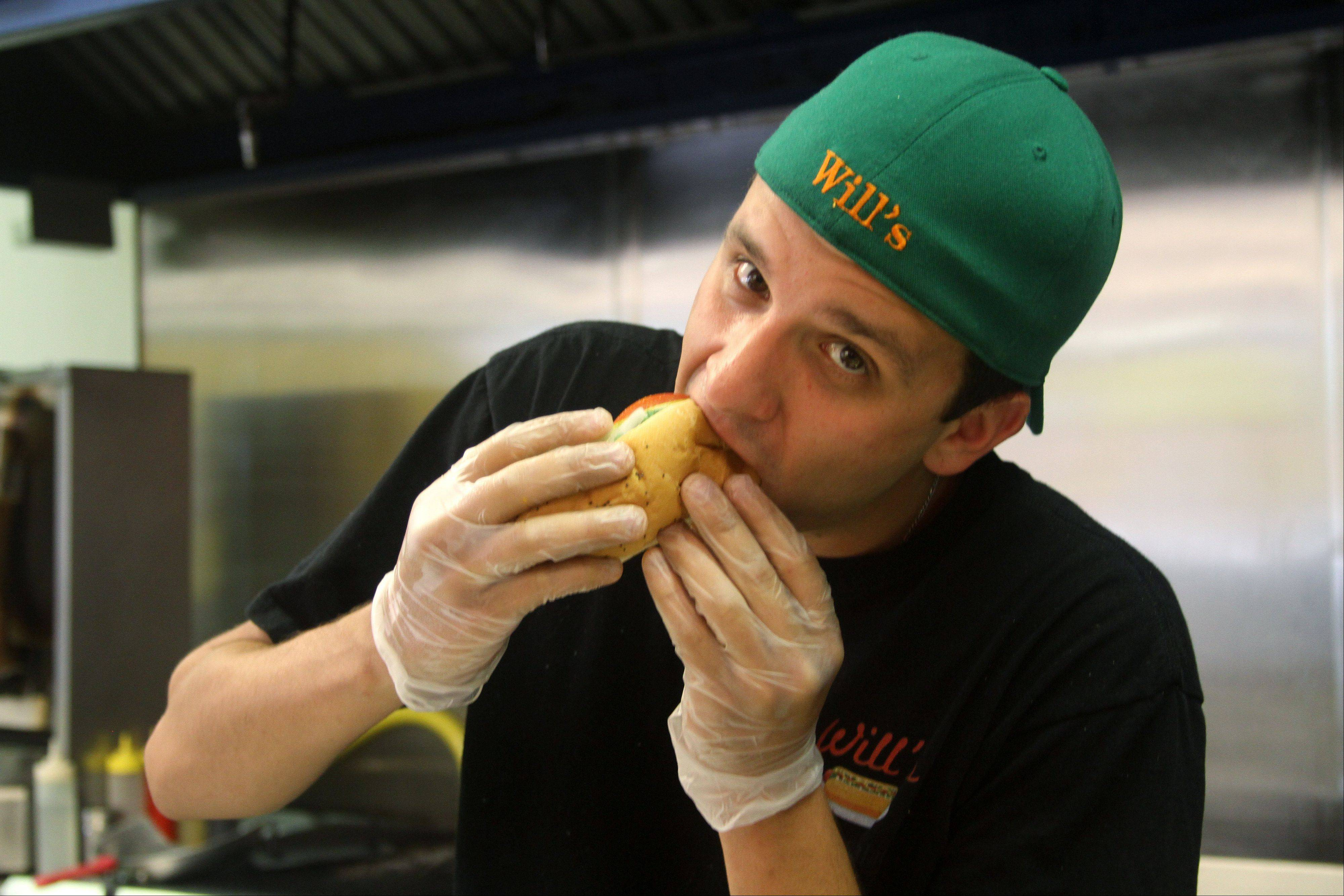 Will Amarantos, the owner of Will's Hot Dog Palace in Carol Stream, takes a bite of a hot dog from his restaurant.