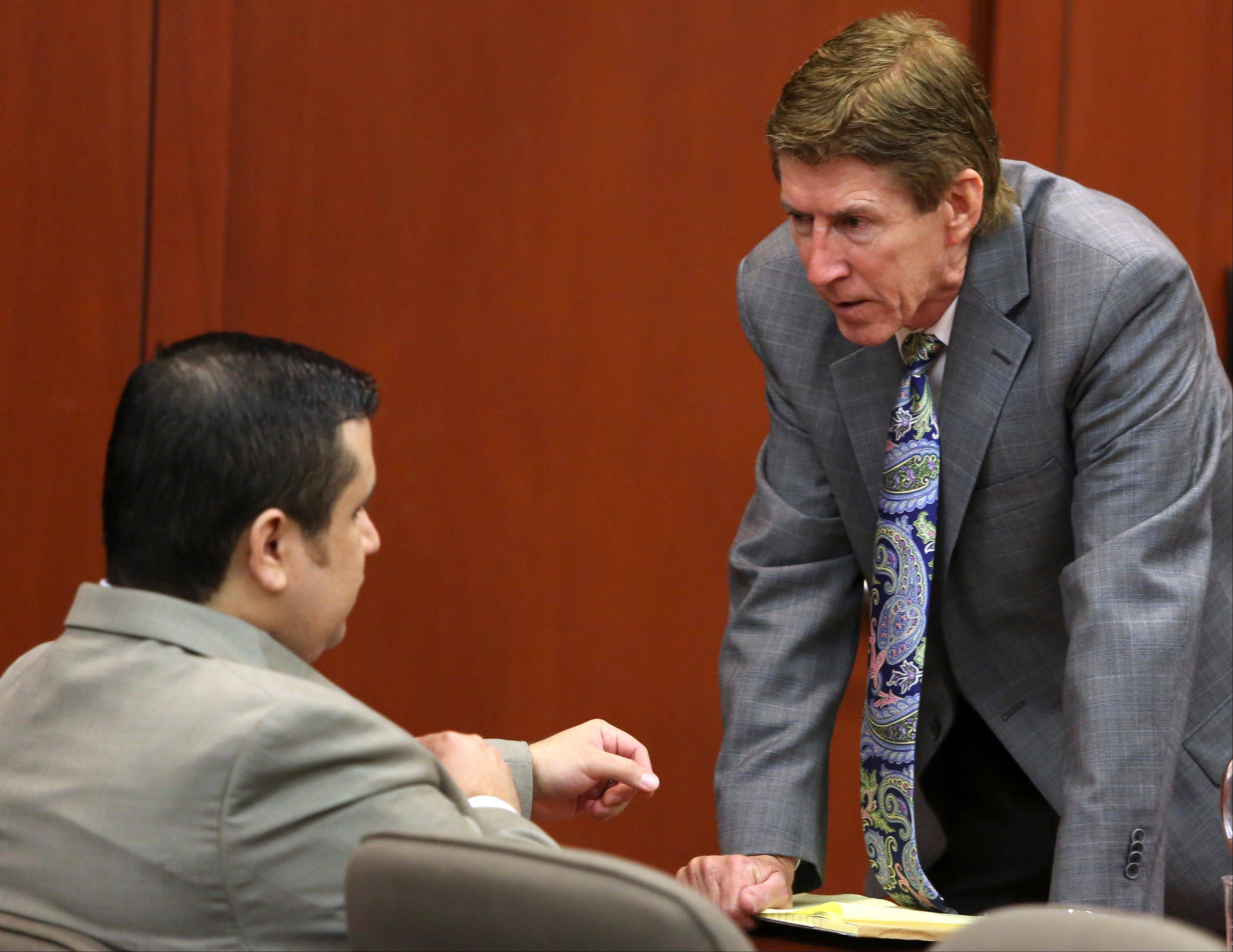 Defense attorney Mark O'Mara, right, speaks with client George Zimmerman during his trial in Seminole County circuit court in Sanford, Fla. Tuesday. Zimmerman has been charged with second-degree murder for the 2012 shooting death of Trayvon Martin.