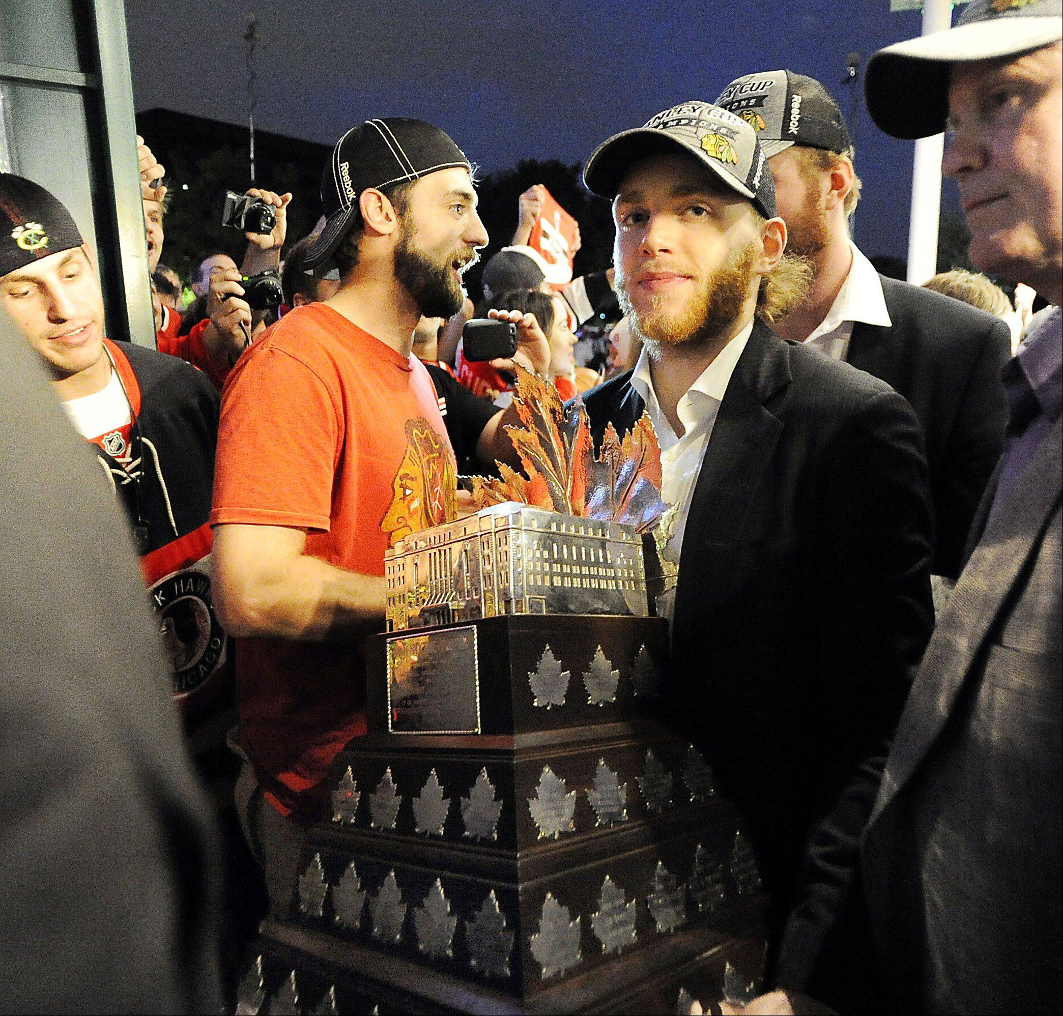 Patrick Kane carries the Conn Smythe Trophy as MVP of the playoffs into Harry Caray's restaurant in Rosemont early Tuesday morning after winning the Stanley Cup championship.