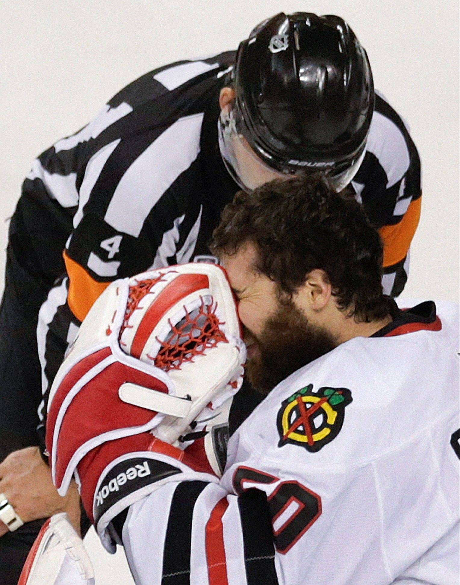 Referee Wes McCauley checks on Blackhawks goalie Corey Crawford during the first period in Game 6 on Monday.
