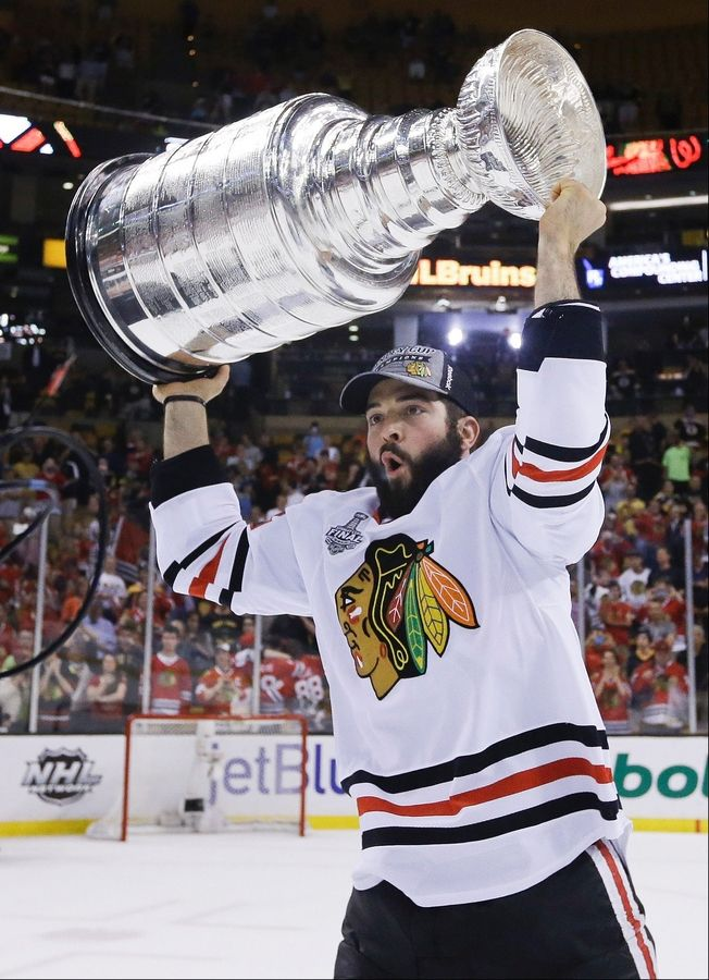 Chicago Blackhawks left wing Brandon Bollig hoists the Stanley Cup after the Blackhawks beat the Boston Bruins 3-2 in Game 6 of the NHL hockey Stanley Cup Finals Monday, June 24, 2013, in Boston.