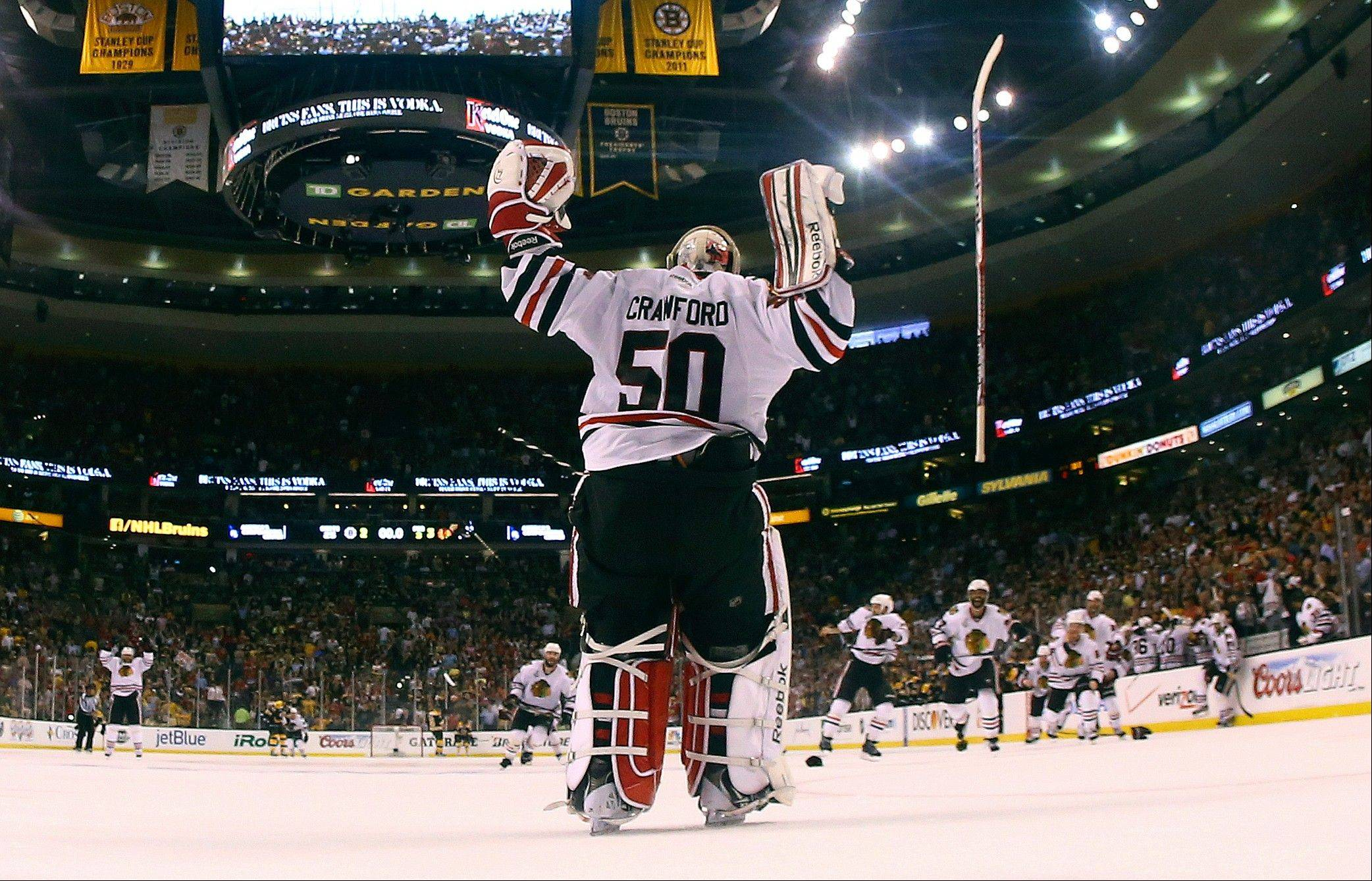 Blackhawks goalie Corey Crawford celebrates with his teammates after the Stanley Cup-clinching Game 6 victory over the Boston Bruins on Monday night.