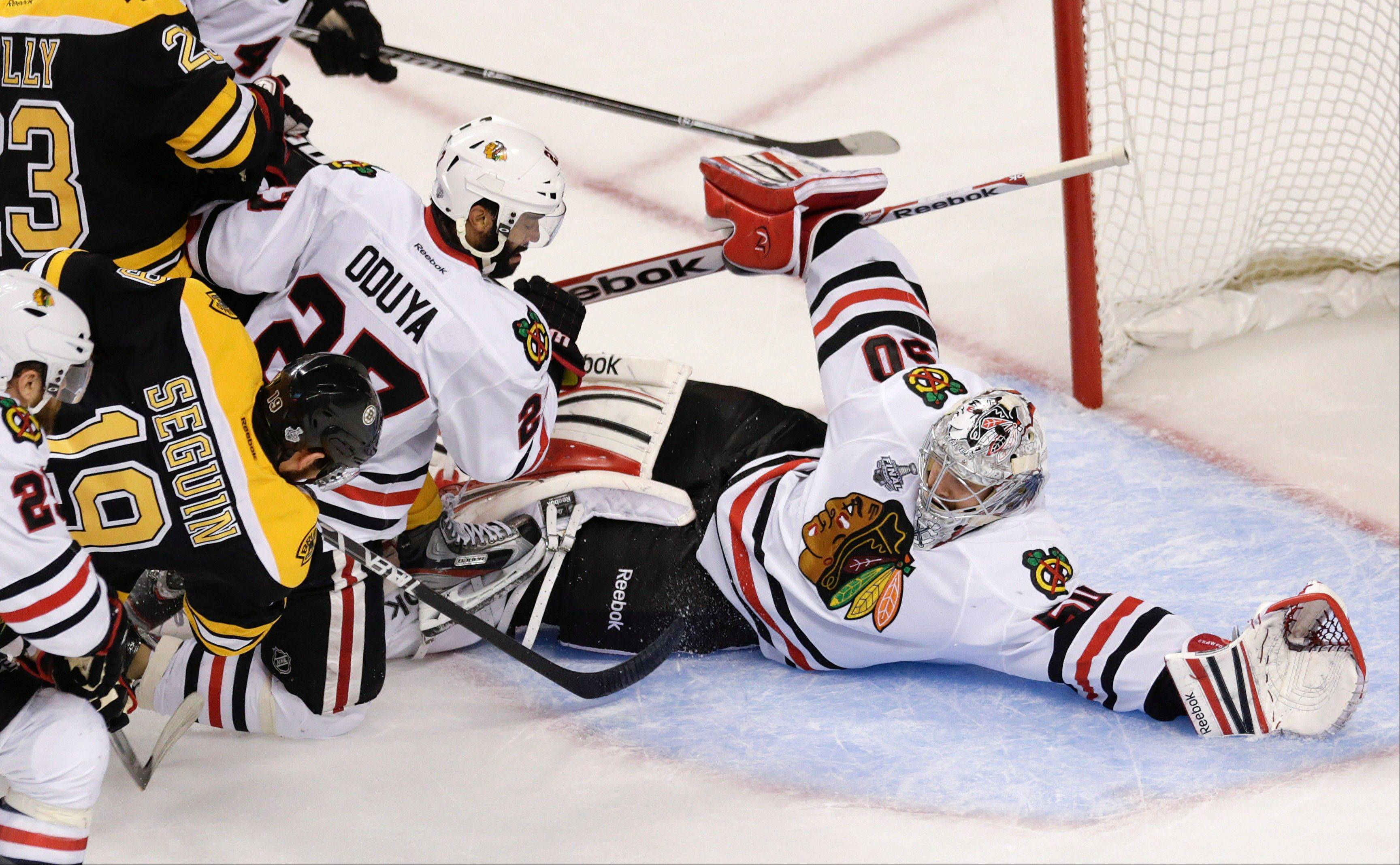 Boston Bruins center Tyler Seguin (19) and Chicago Blackhawks defenseman Johnny Oduya (27), of Sweden, careen into Chicago Blackhawks goalie Corey Crawford (50) during the first period in Game 6 of the NHL Stanley Cup Finals Monday in Boston.